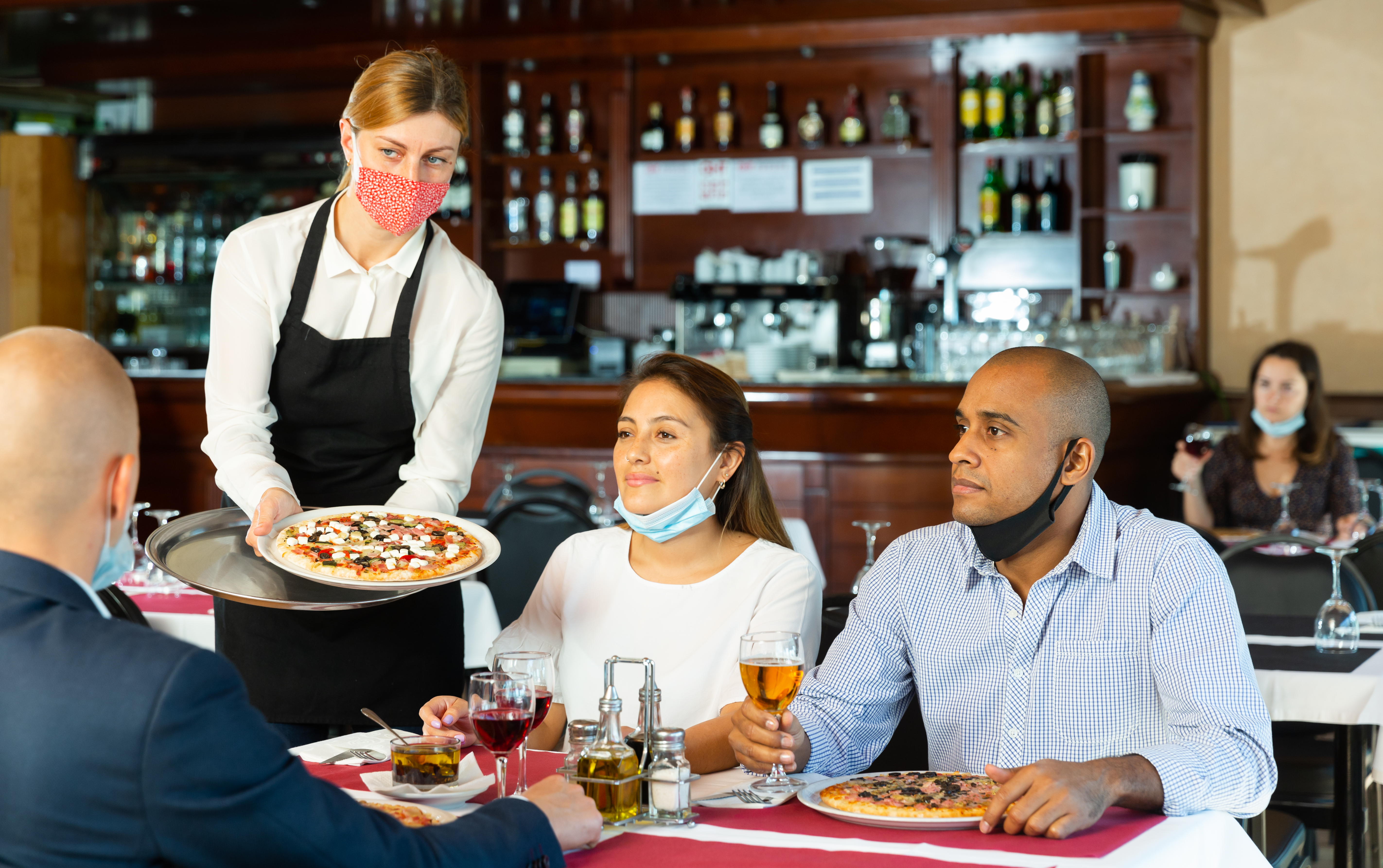A waitress with a mask dropping off pizza to a table of four.