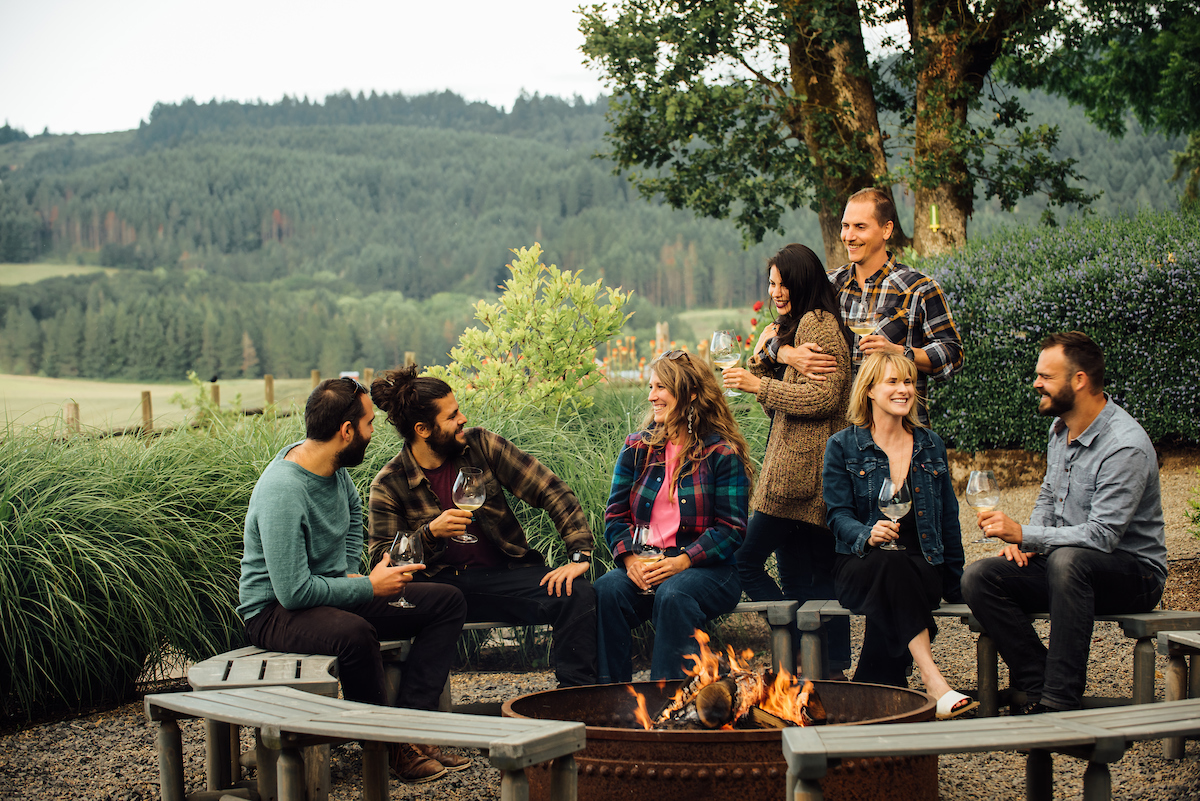 A group of 20somethings and 30 somethings sit around an outdoor firepit with glasses of wine, surrounded by fields and farmland.