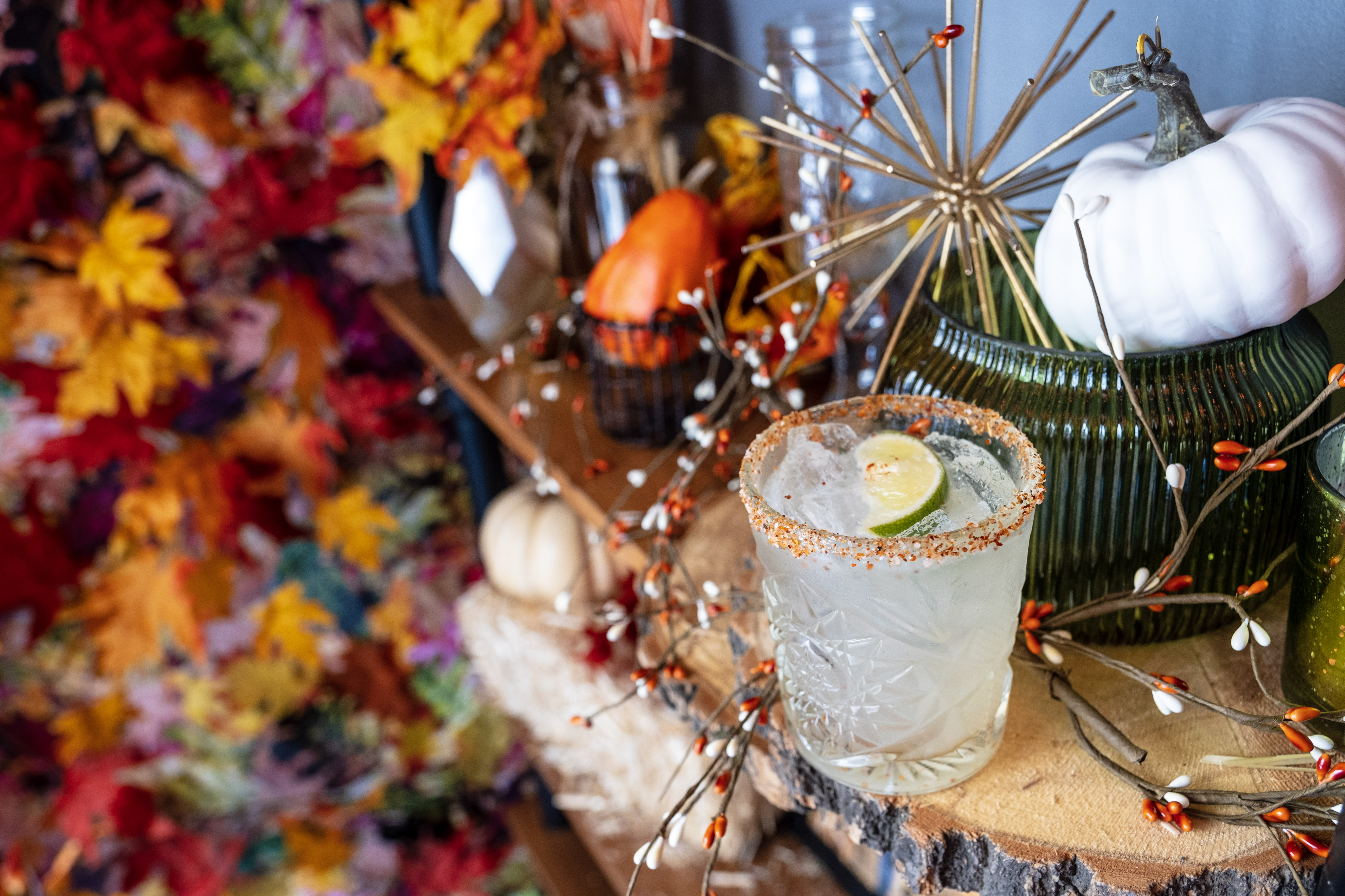 A cocktail in a short glass with a sugared rim and lime garnish on a table with a backdrop of colorful leaves and a round white gourd.