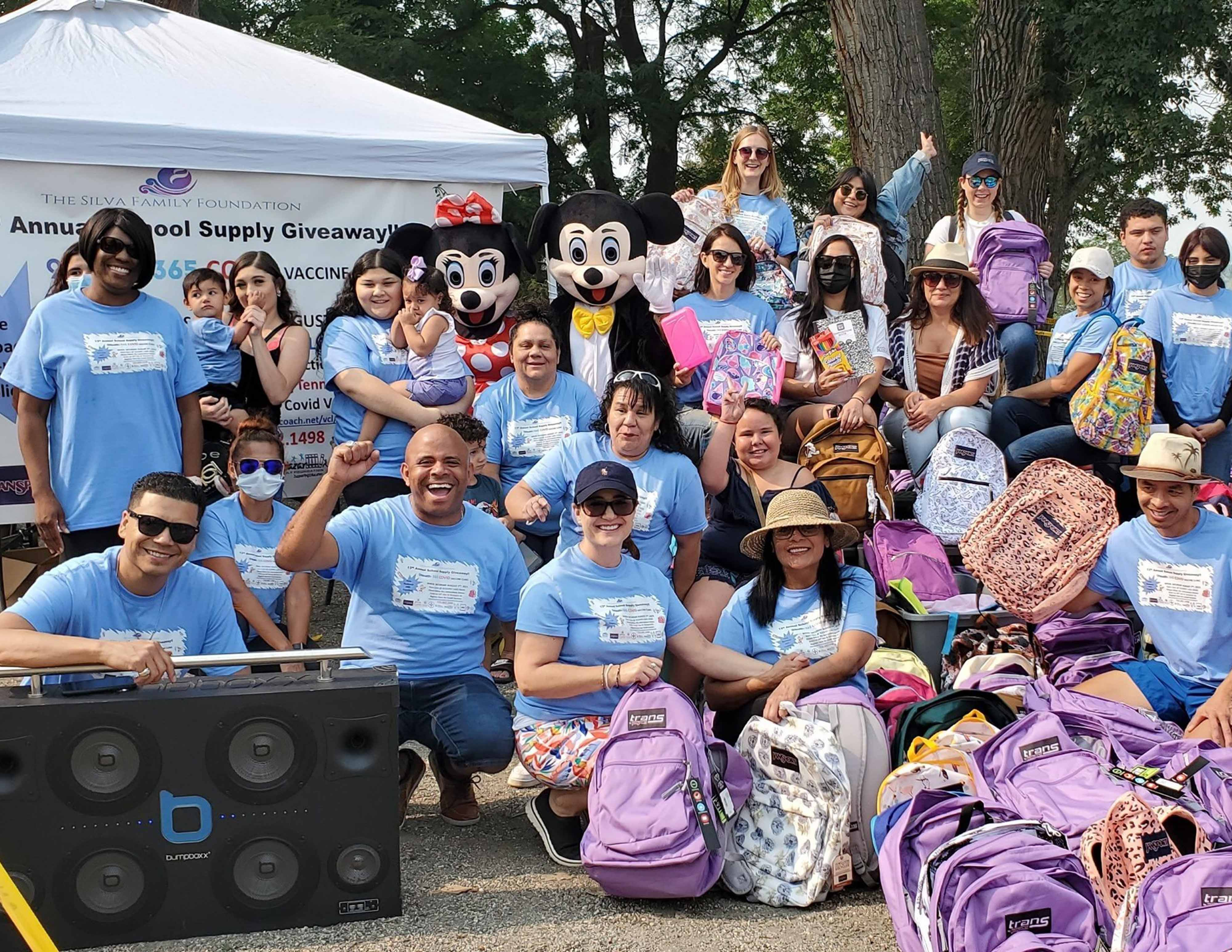 Denver School Board candidate Jose Silva, center left, poses with about two dozen people during a backpack and school supply drive. Many are wearing sky blue T-shirts and two are dressed as Mickey Mouse.