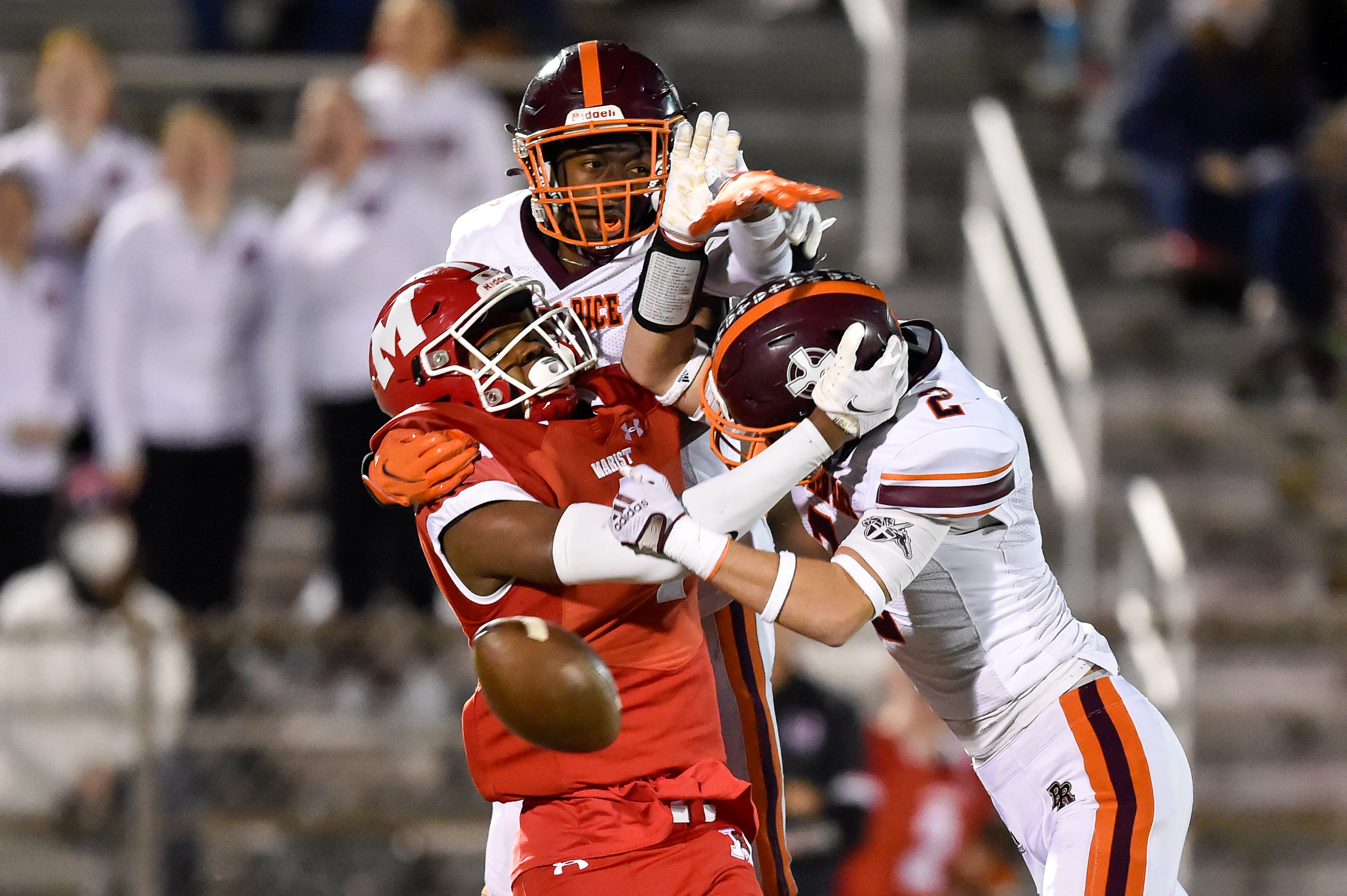 Brother Rice's Luke Niksic (2) and Sean Kinard (12) stop Marist's Ryan Sims (4) from catching a pass.