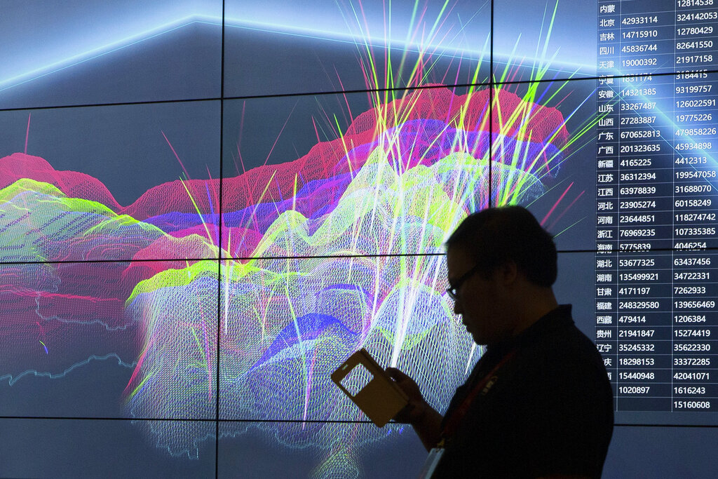 An attendee walks past a live visualization of internet attacks across China.