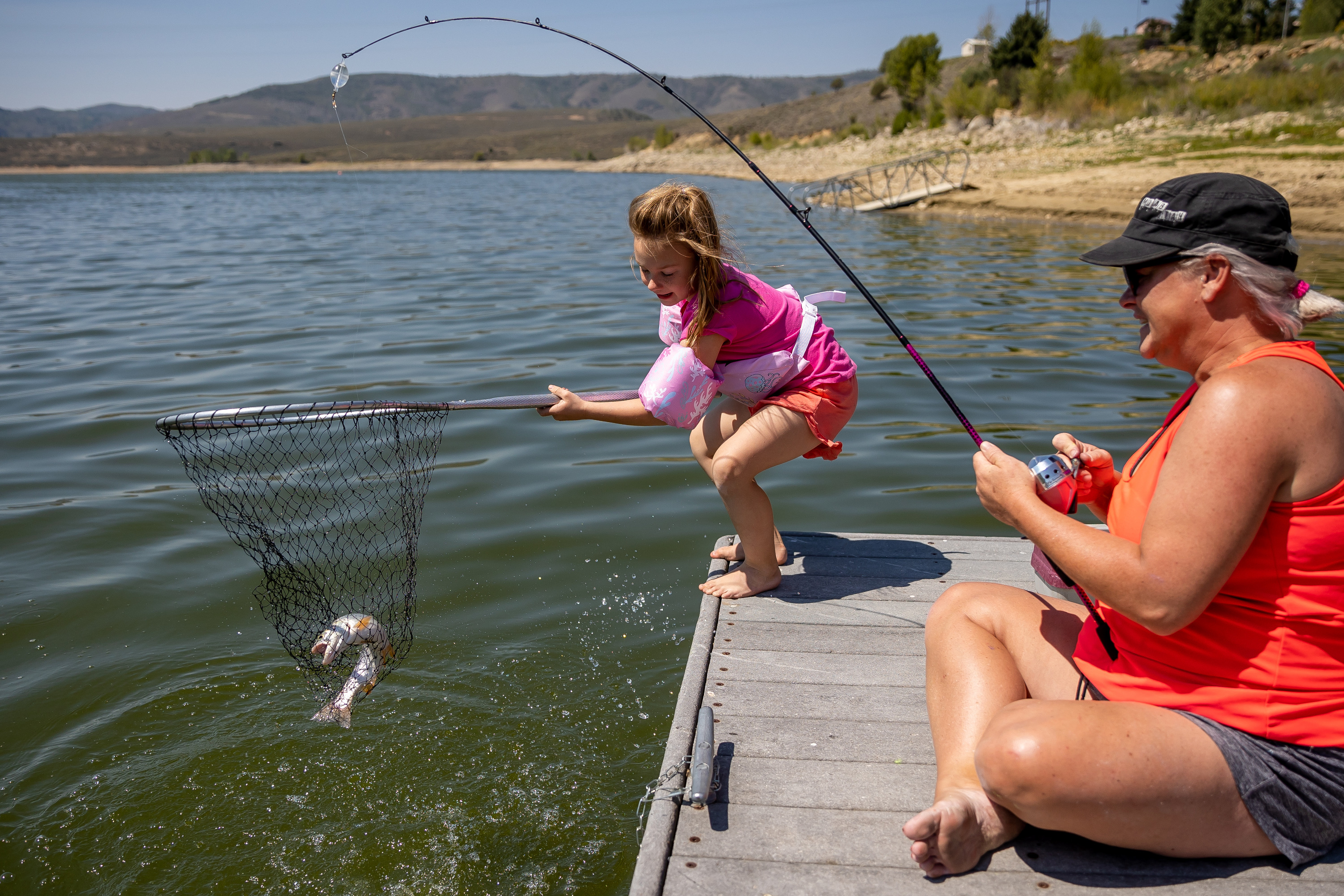 Presley Morse, 6, helps land a cutthroat trout while fishing with her mother, Jill Gilson, at Scofield State Park on Friday, Aug. 27, 2021.