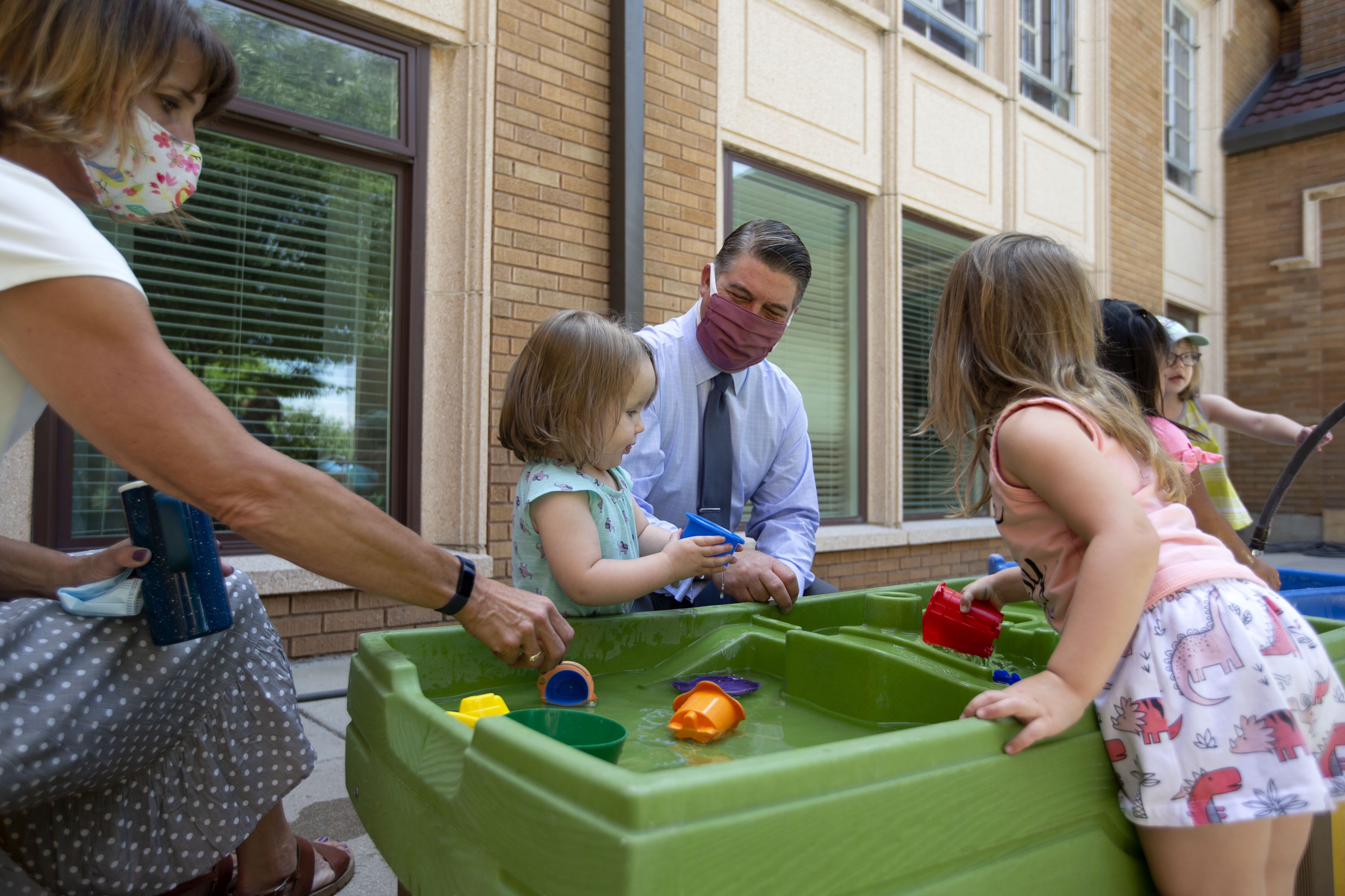 Leaders of First Baptist Child Development Center in Salt Lake City play outside with children in June 2020.