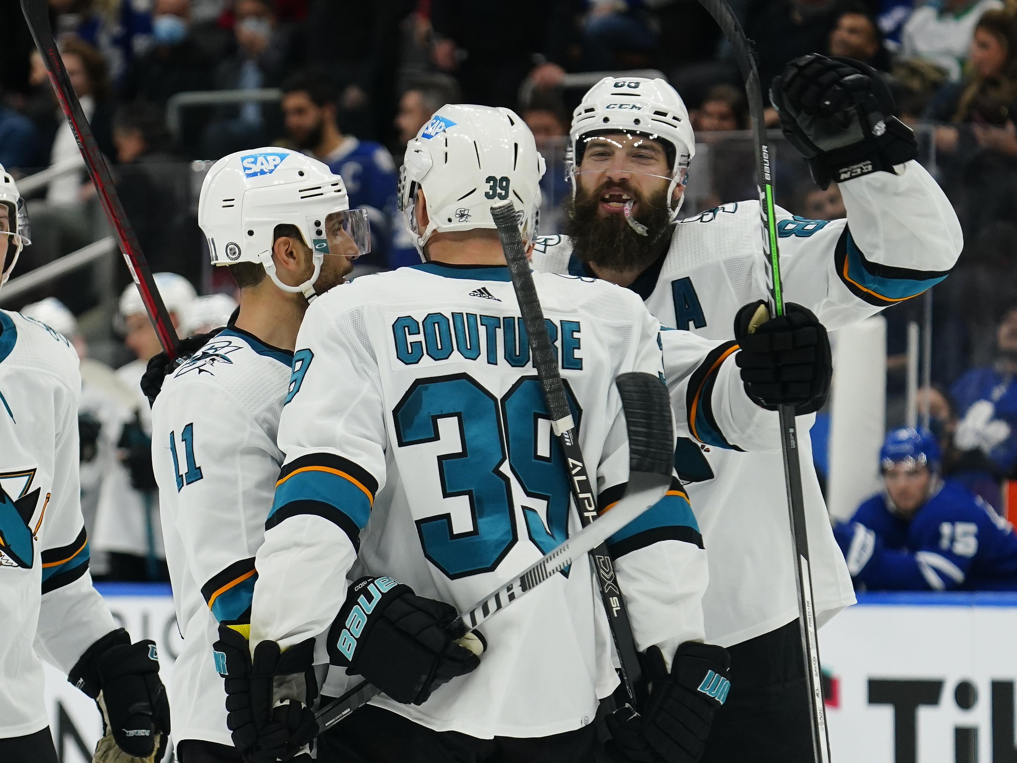 Oct 22, 2021; Toronto, Ontario, CAN; San Jose Sharks defenseman Brent Burns (88) and forward Andrew Cogliano (11) congratulate forward Logan Couture (39) on his second goal of the game against the Toronto Maple Leafs during the third period at Scotiabank Arena.