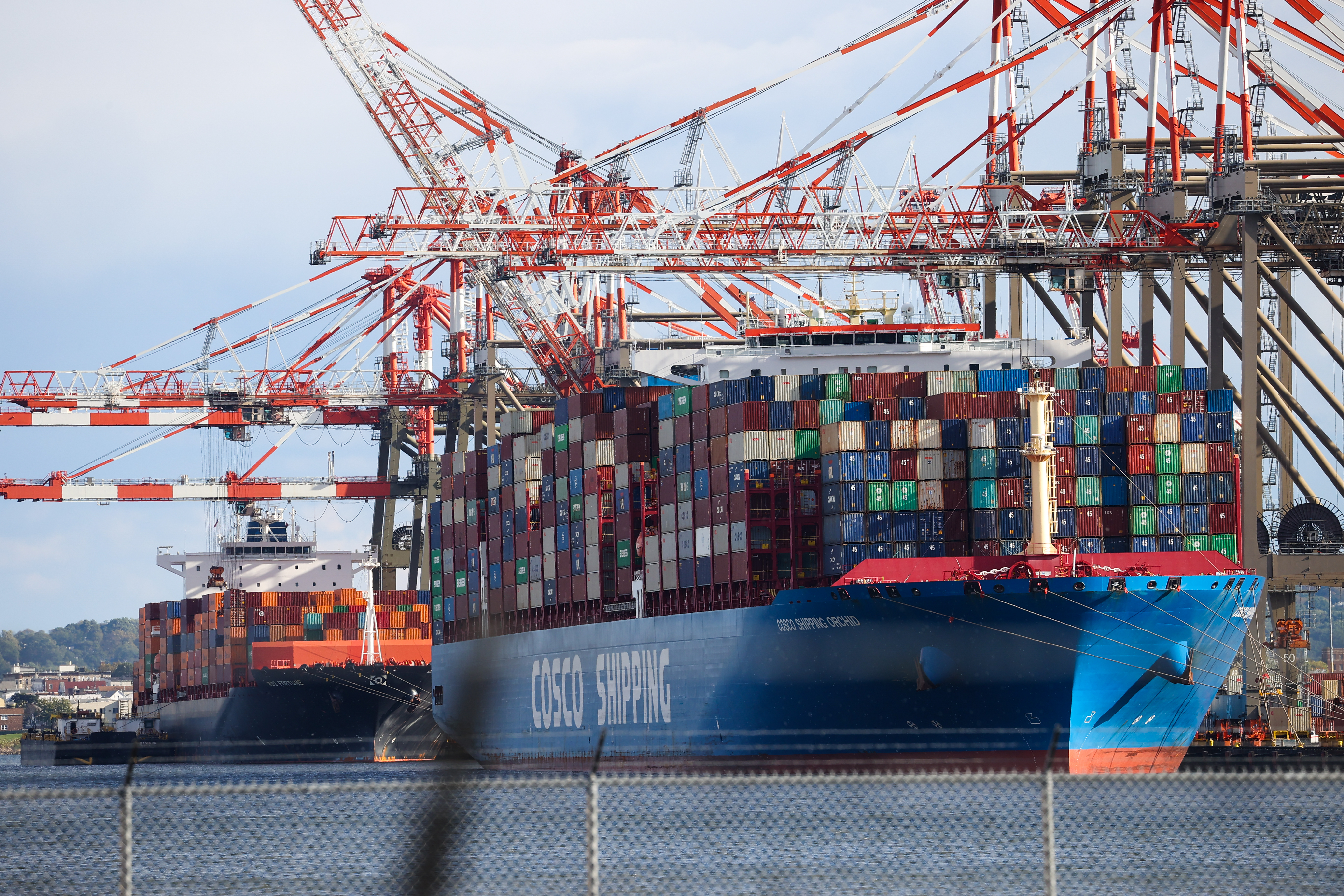 A fully loaded container ship with container cranes overhead is docked at a port in Newark, New Jersey.