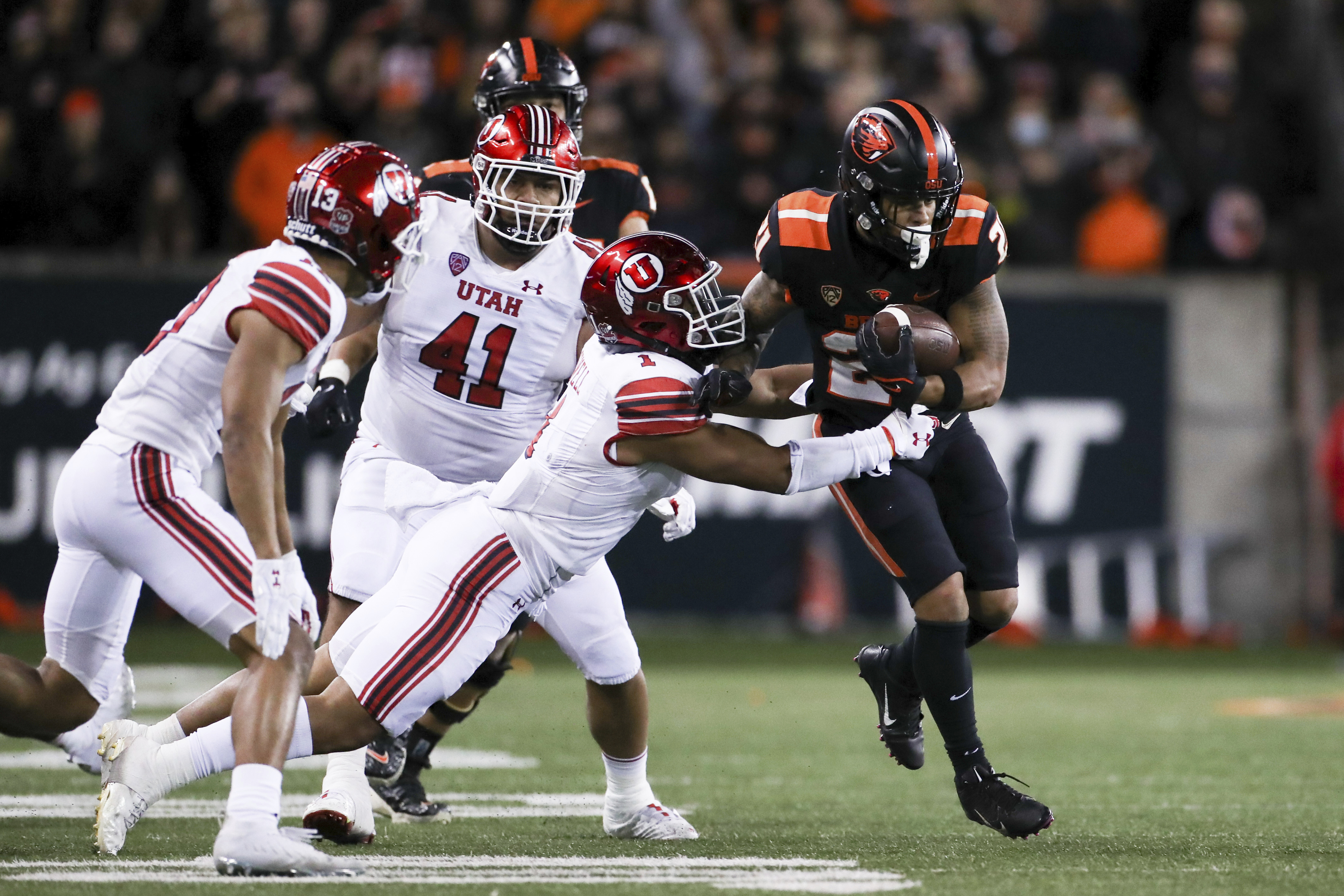 Oregon State running back Trey Lowe, wearing black, is brought down by Utah linebacker Nephi Sewell
