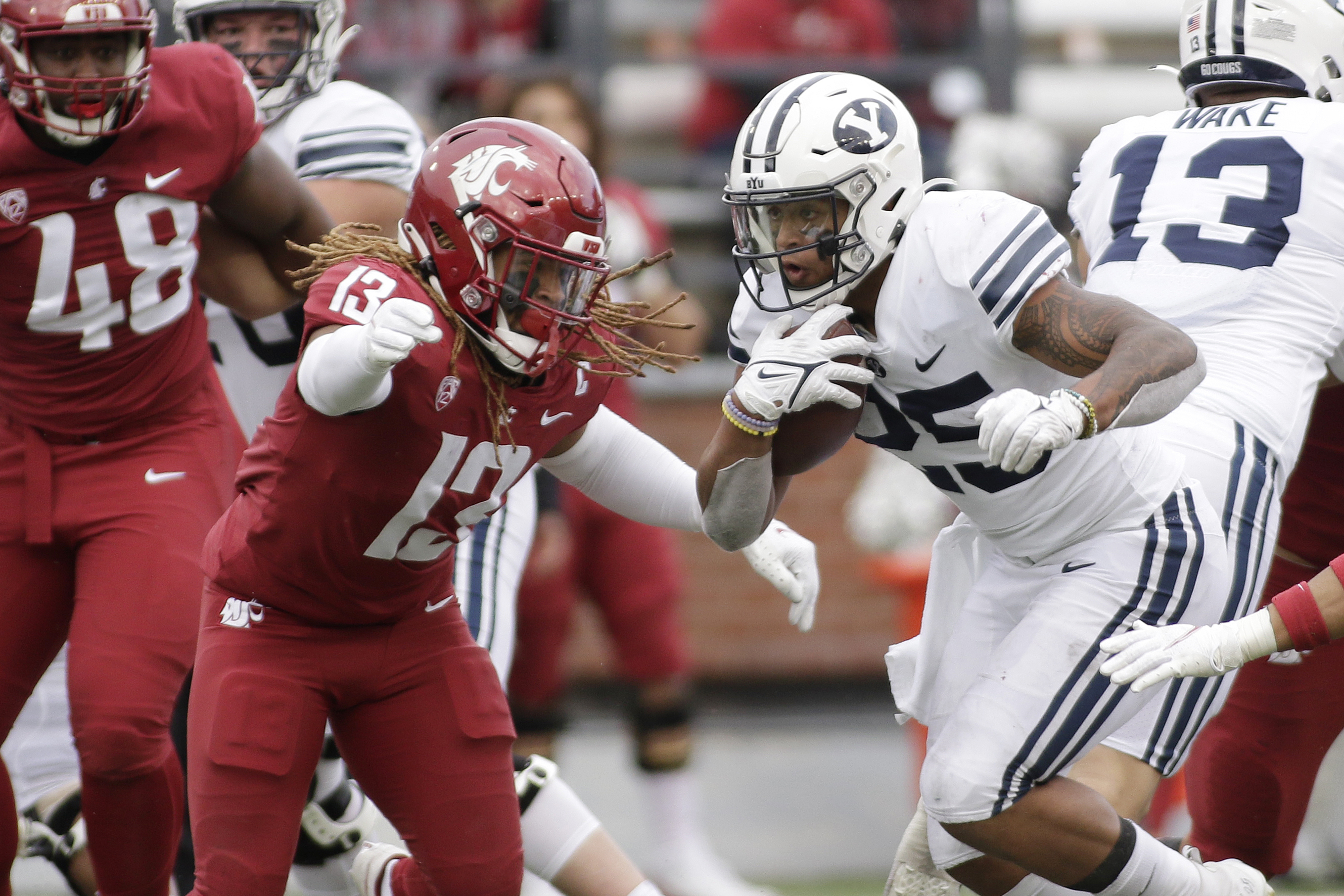 BYU running back Tyler Allgeier, right, carries the ball while pressured by Washington State linebacker Jahad Woods.