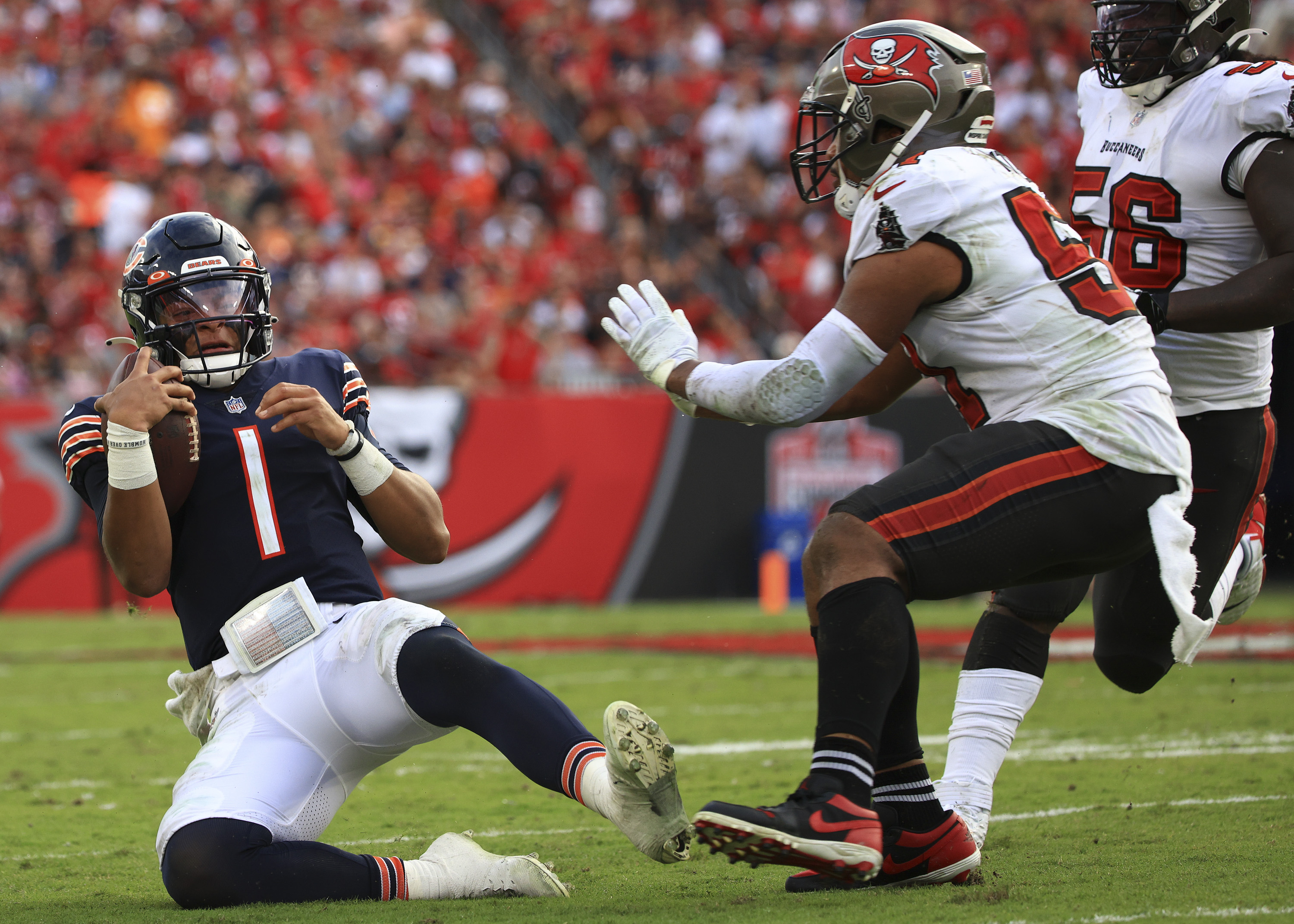 Quarterback Justin Fields slides with the ball in the second quarter of the Bears' 38-3 loss to Tampa Bay.