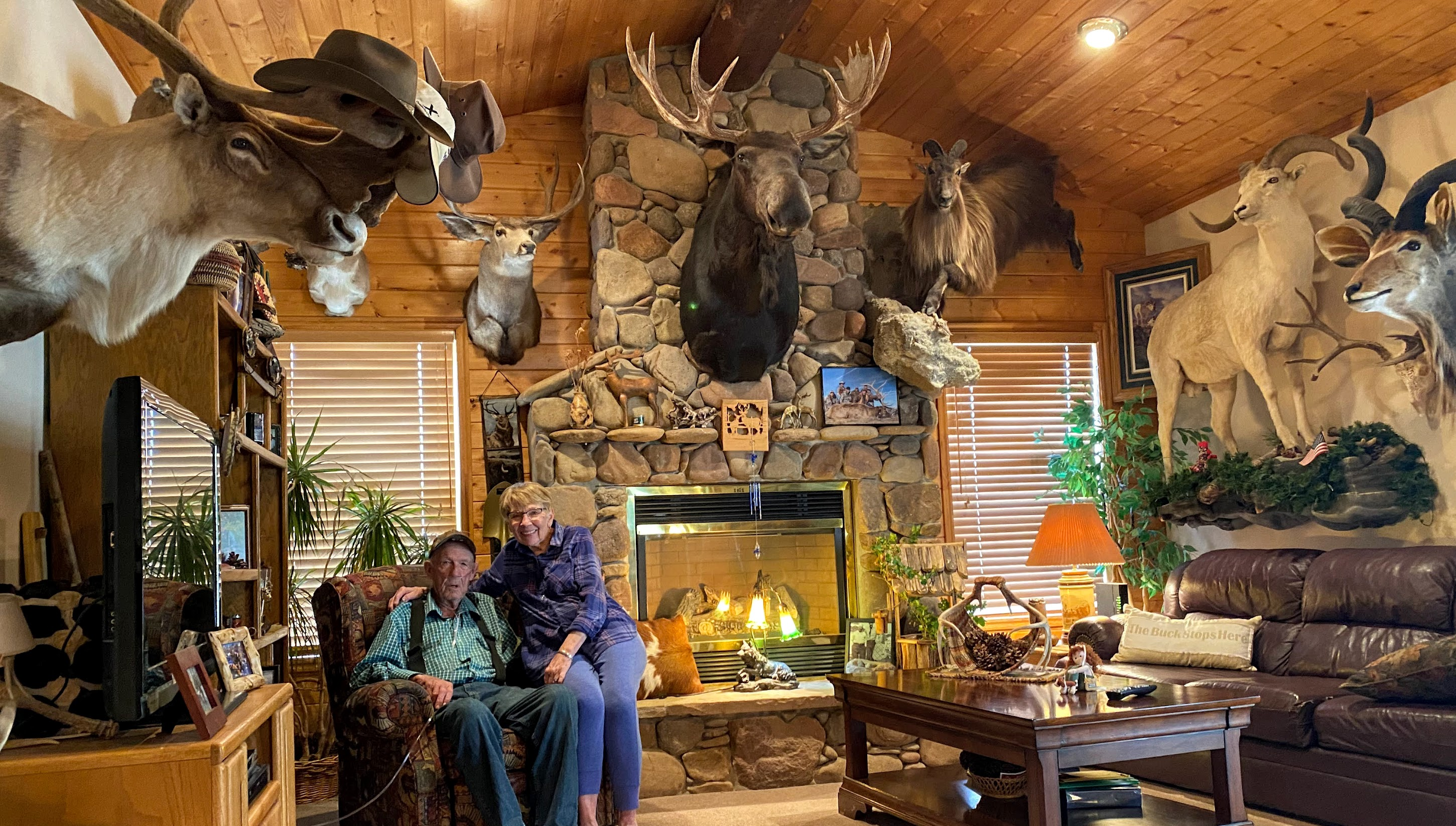 Jerry and Carolyn Christensen sit in Jerry's big game trophy room at their home in Heber City.