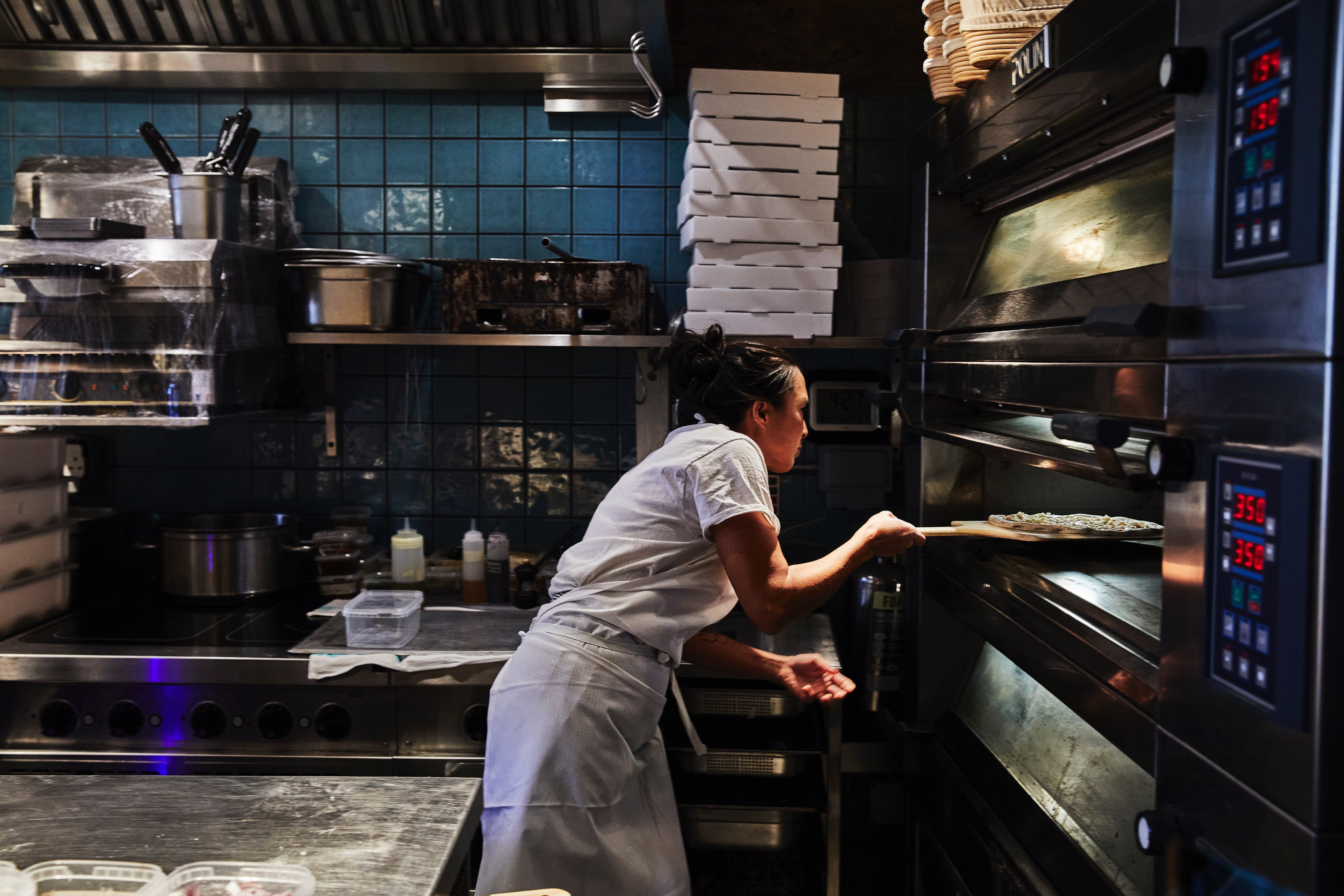 Pam Yung of ASAP pizza, at Flor, slides a pizza into a deck oven using a wooden peel