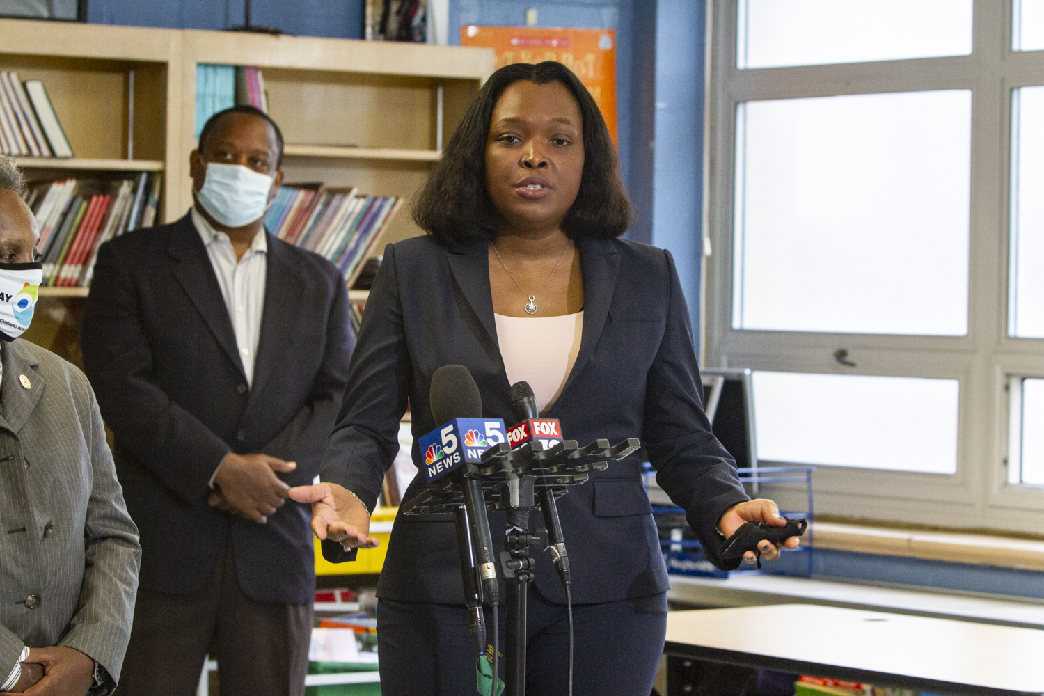 School chief Janice Jackson speaking into microphones at a press conference.