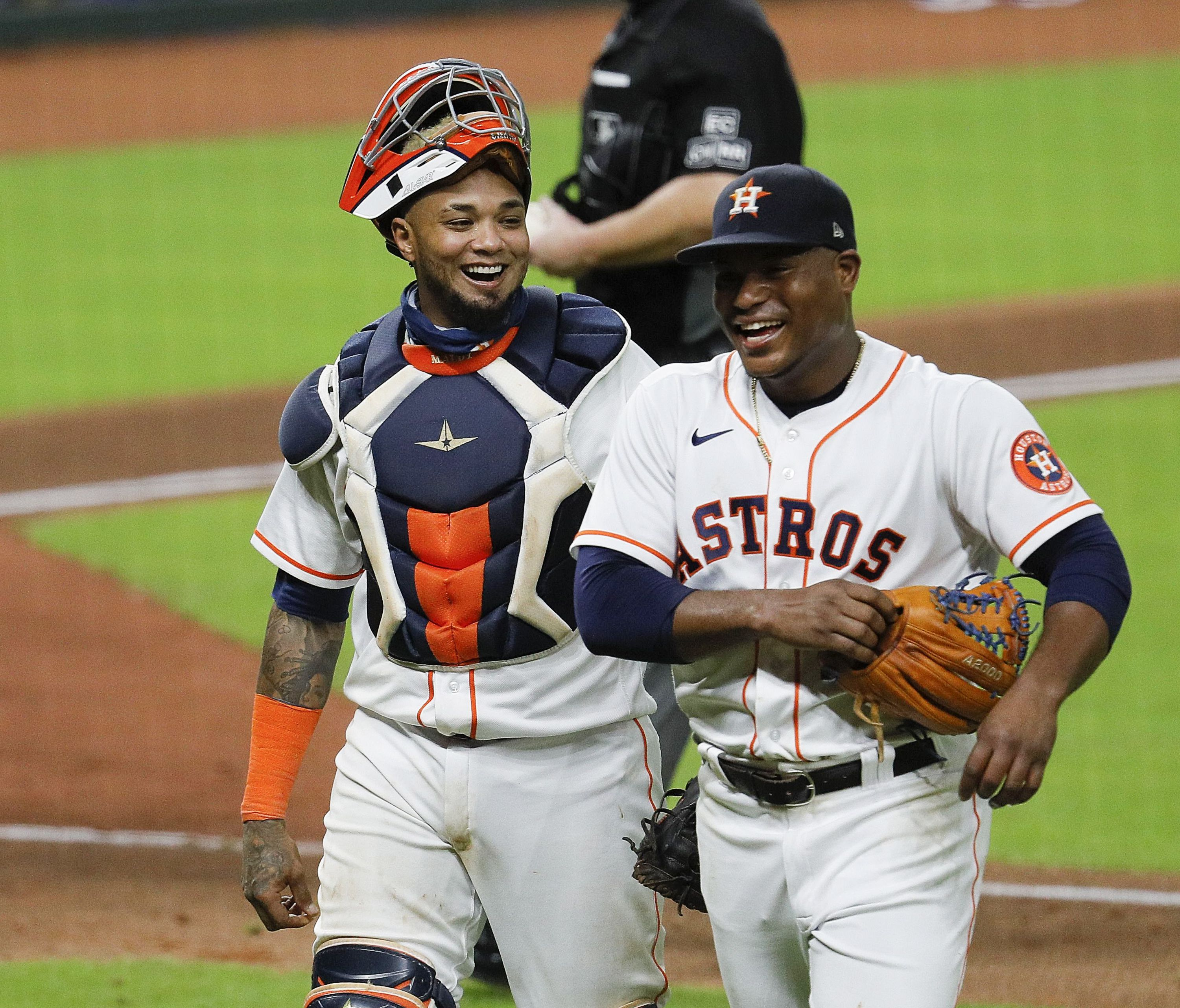 Framber Valdez #59 of the Houston Astros and Martin Maldonado #15 laugh after a ground ball was back up the middle and almost hit Valdez in the sixth inning against the Texas Rangers at Minute Maid Park on September 17, 2020 in Houston, Texas.
