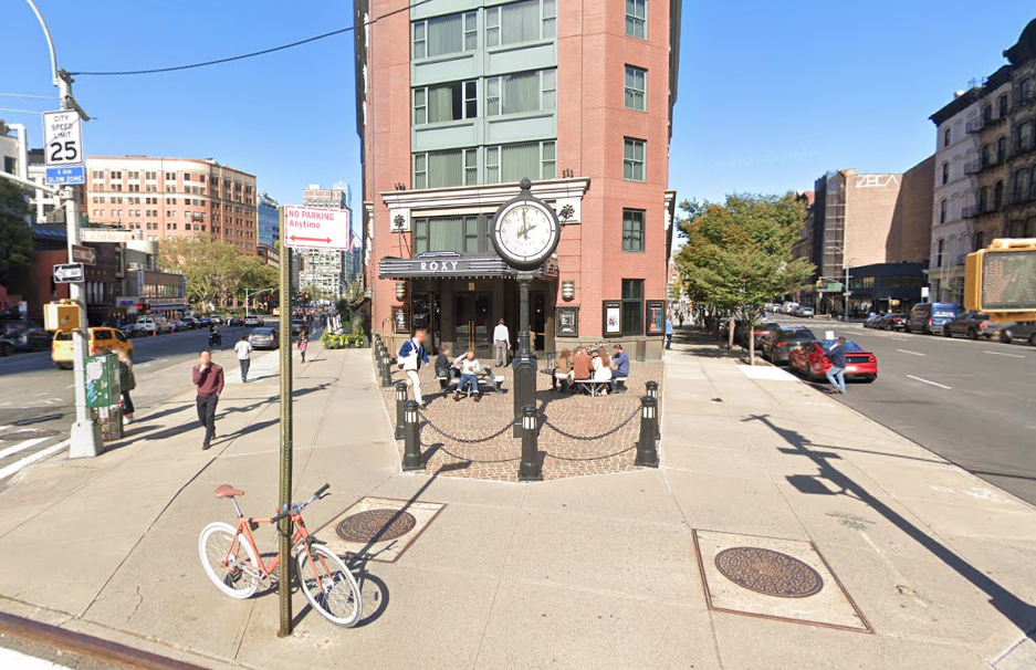 An exterior shot of a building on a sunny day with a standing clock outside and people walking by on the sidewalk.