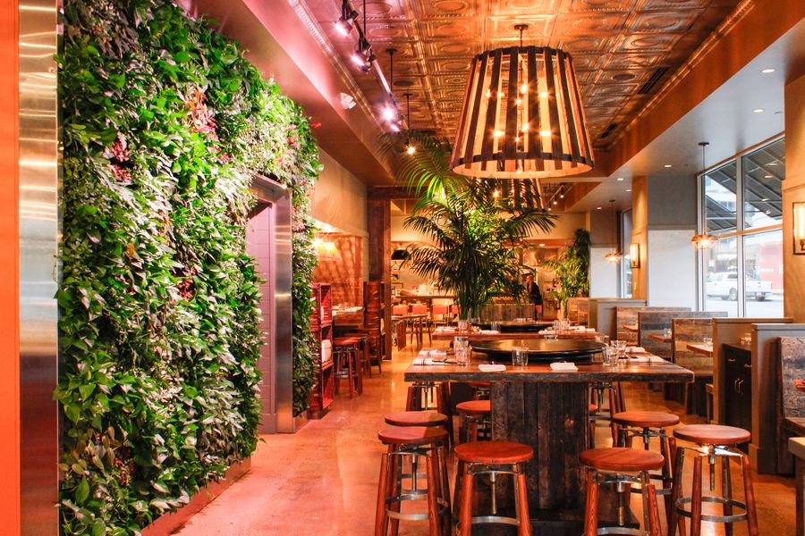 A colorful restaurant interior features orange and gold accents and a wall covered in green plants