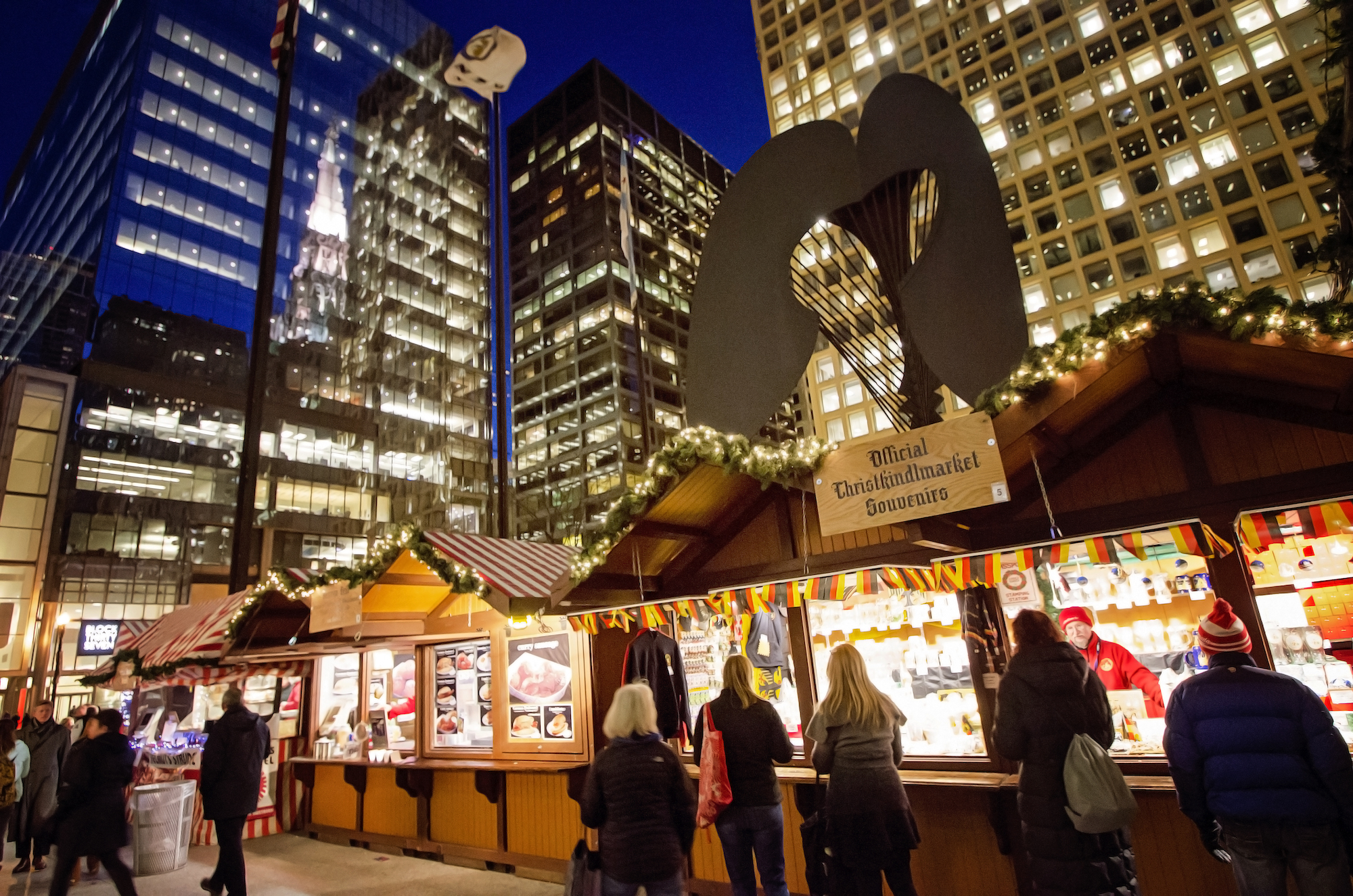 Visitors line up in front of a row of brightly-lit booths with lit-up skyscrapers in the background