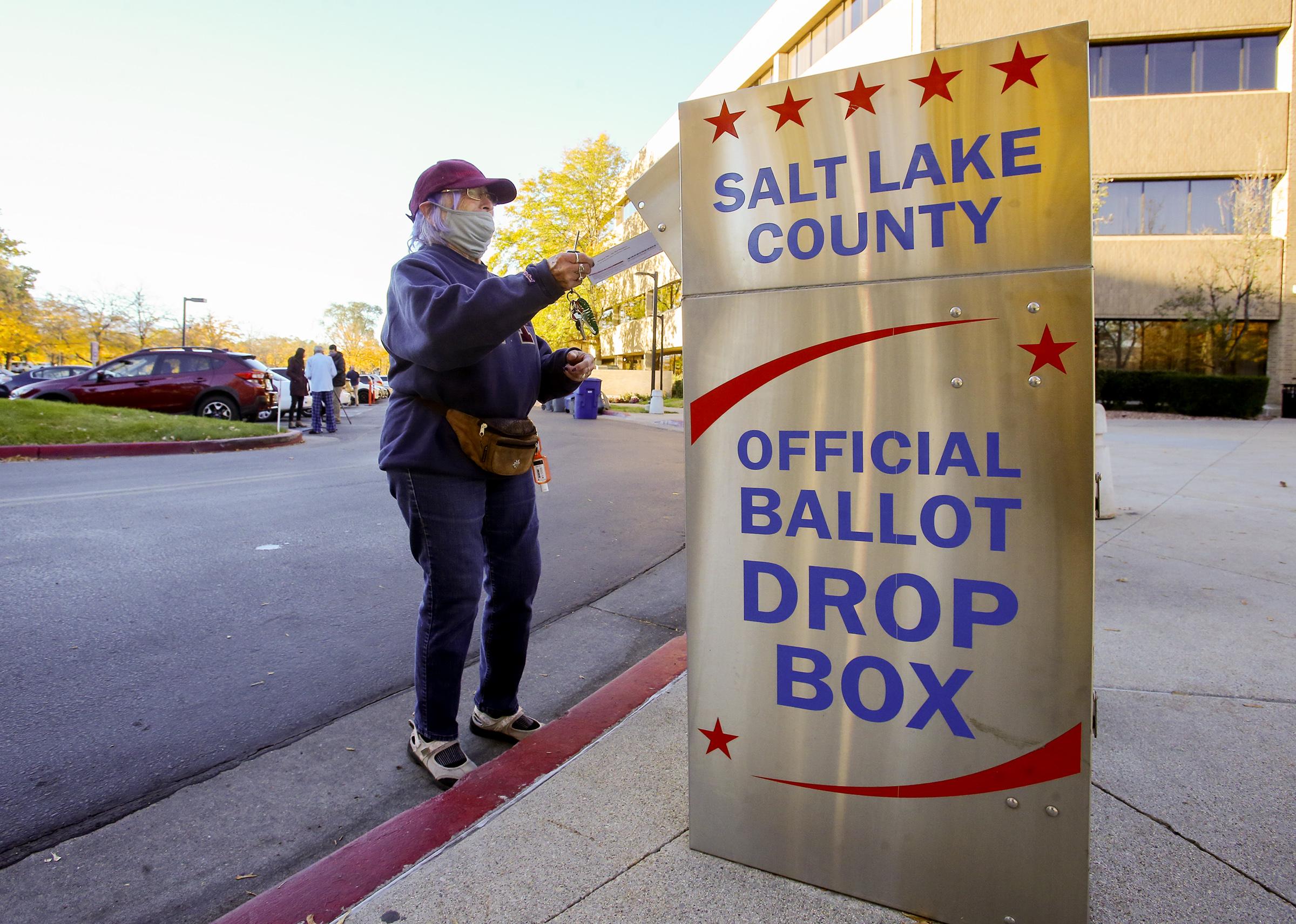 A voter puts a ballot into an official drop box.