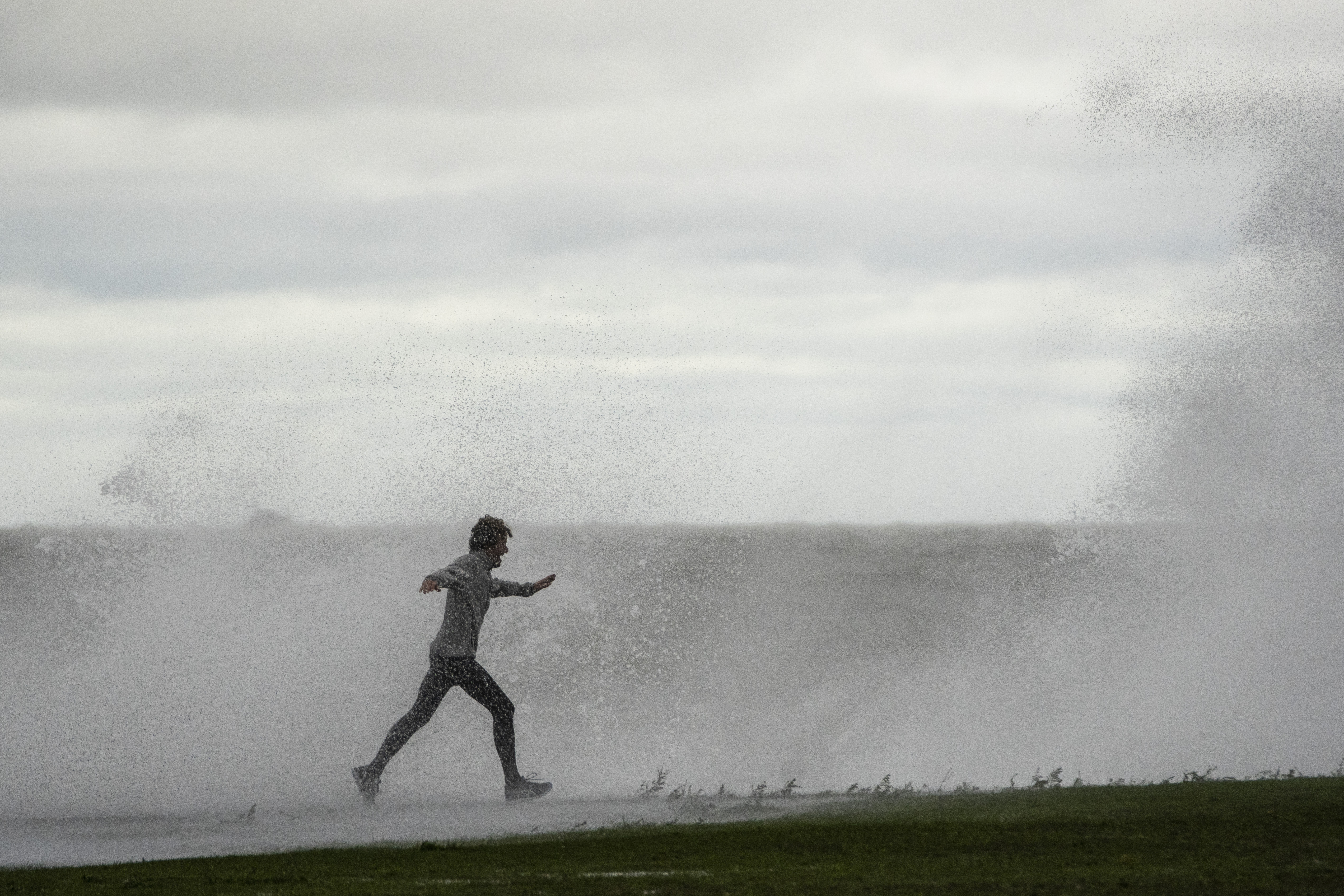 A jogger gets hit with a high wave Monday afternoon on the Lakefront Trail near West Fullerton Avenue on the North Side.