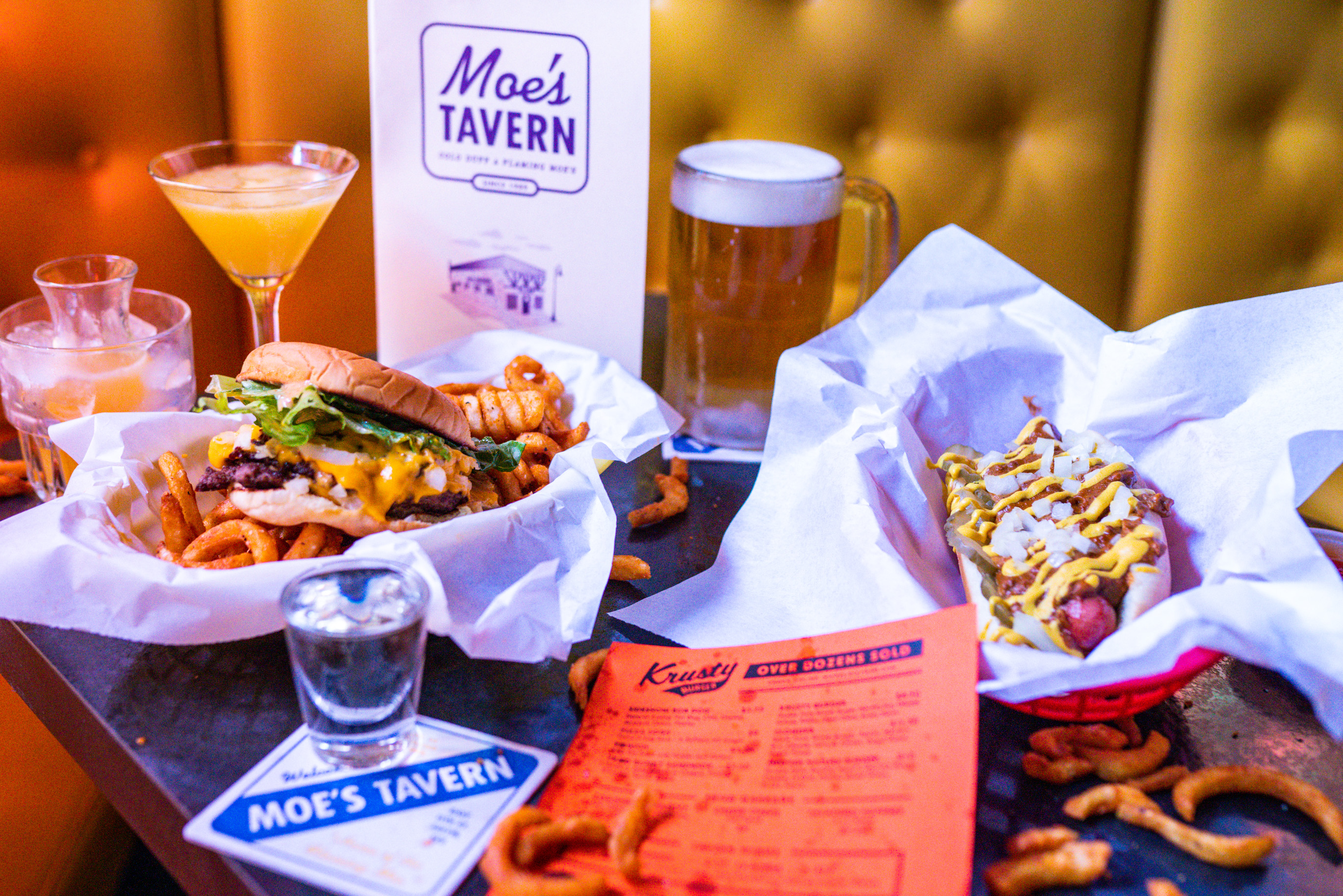 A table with a basket of burgers and fries, and another basket of a hot dog with cheese and sauce, with cocktails and menus.