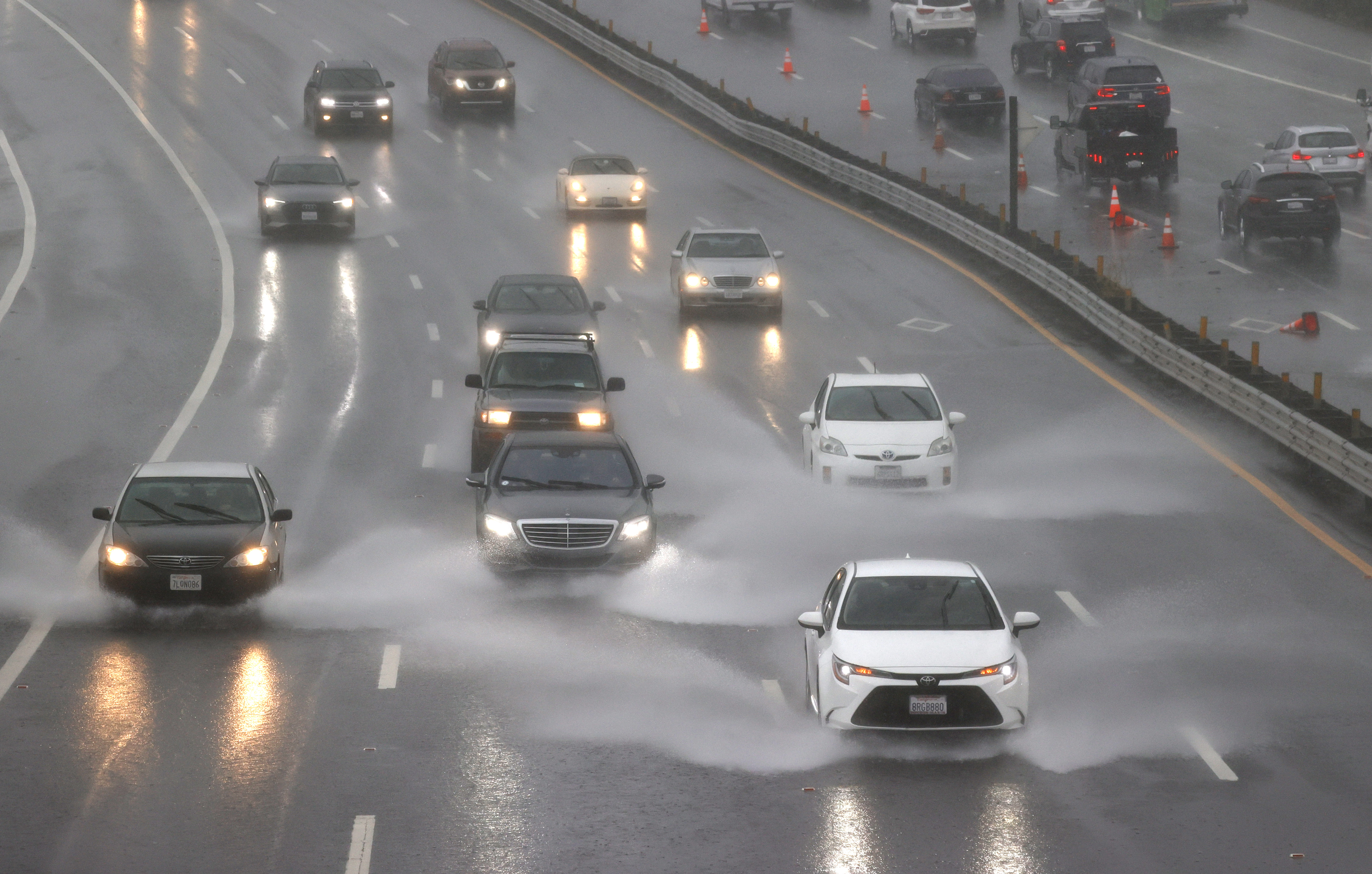Cars driving on a freeway in an intense rainstorm.
