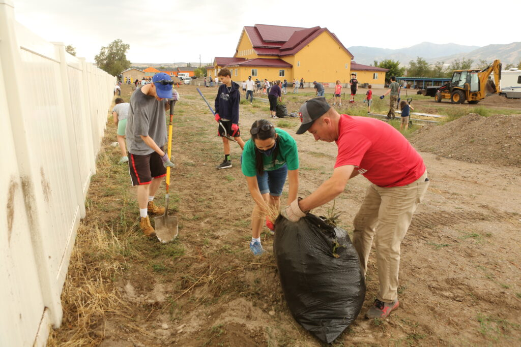Community members clean the grounds of the Wat Lao Salt Lake Buddharam. Members from multiple stakes and civic volunteers brought in heavy equipment to level the parking lot and clean away the weeds in preparation for future paving.