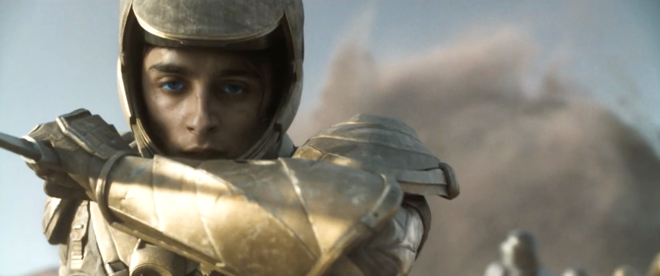 a close-up of Paul (Timothee Chalamet) wearing gold armor in Dune