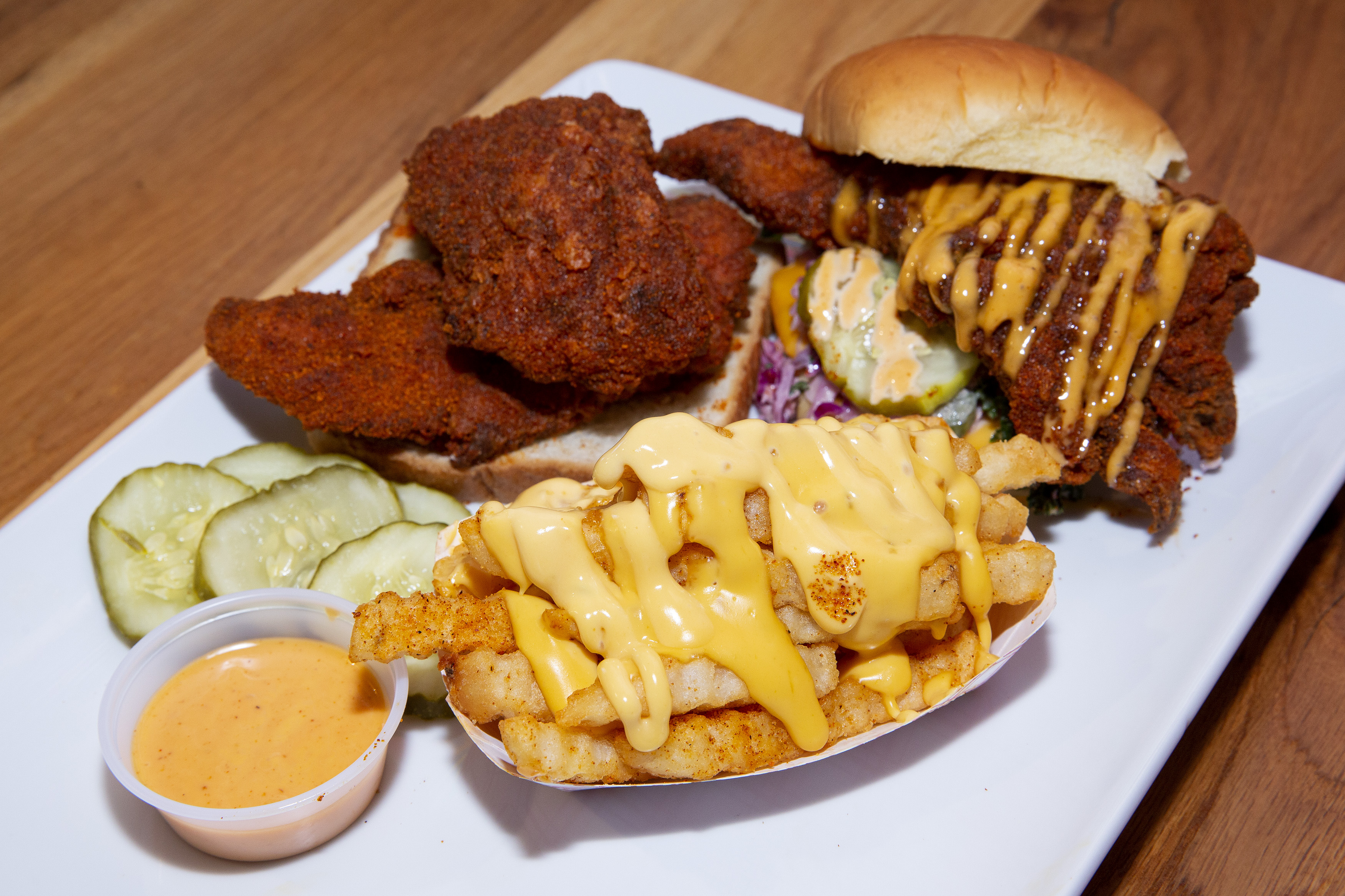 A white plate of two hot chicken sandwiches and a serving of crinkle-cut fries drizzled with cheese sauce.