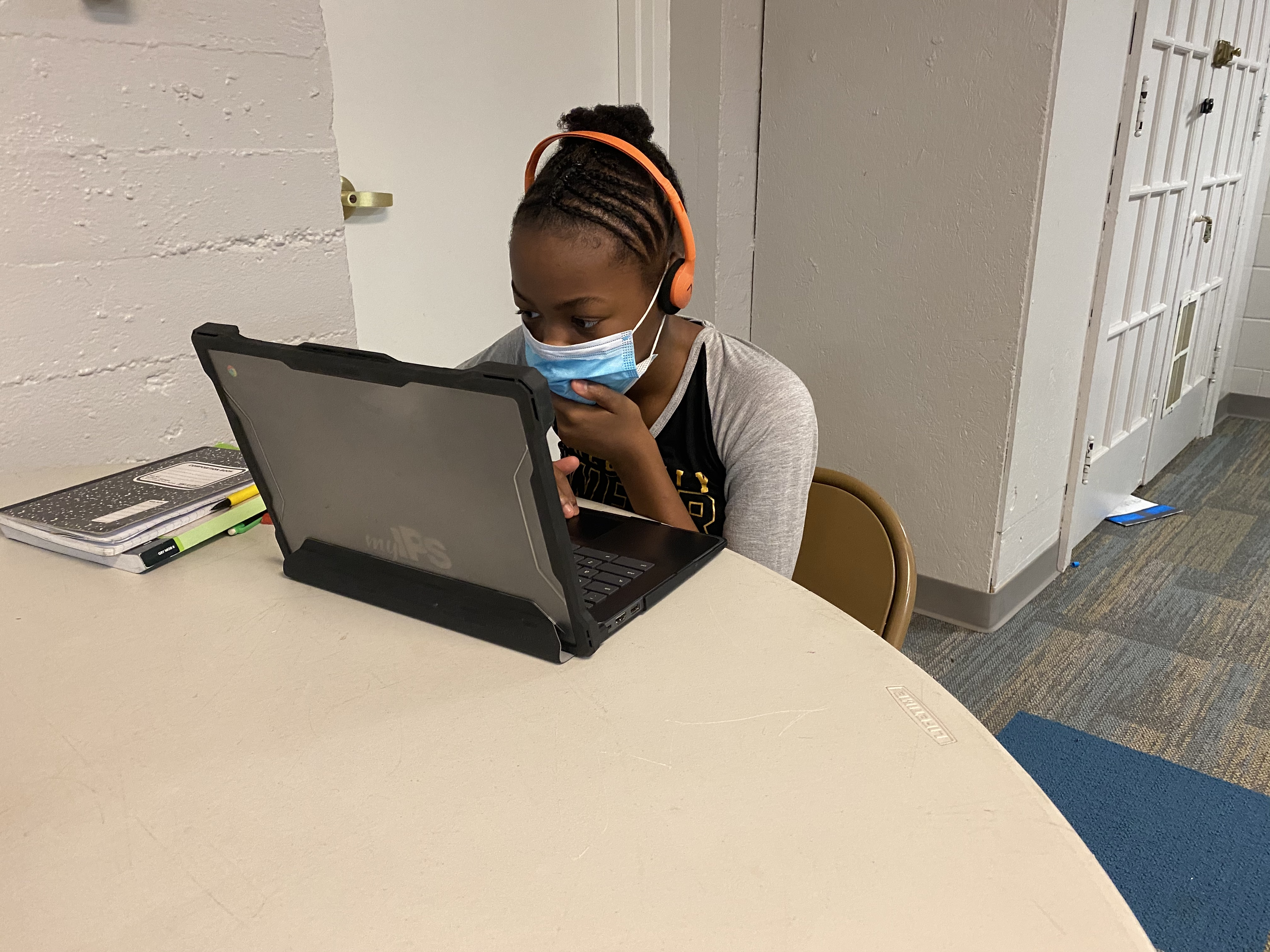 A student with a mask covering her face sits at a table looking at a laptop screen