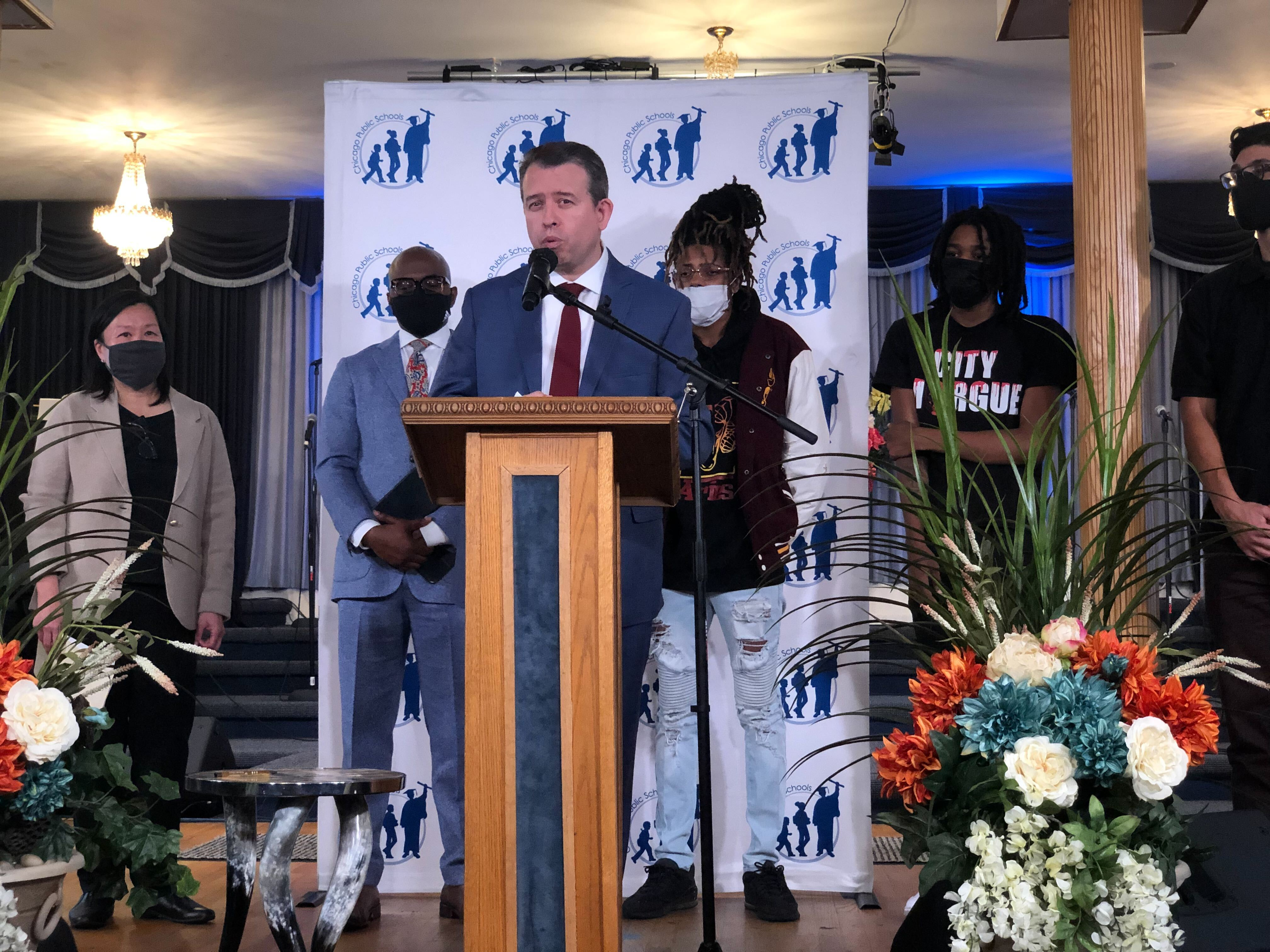 Flanked by district officials and local students, Chicago Public Schools CEO Pedro Martinez stands at a podium in a suit and tie and announces an expansion of a youth violence intervention program Choose for Change.