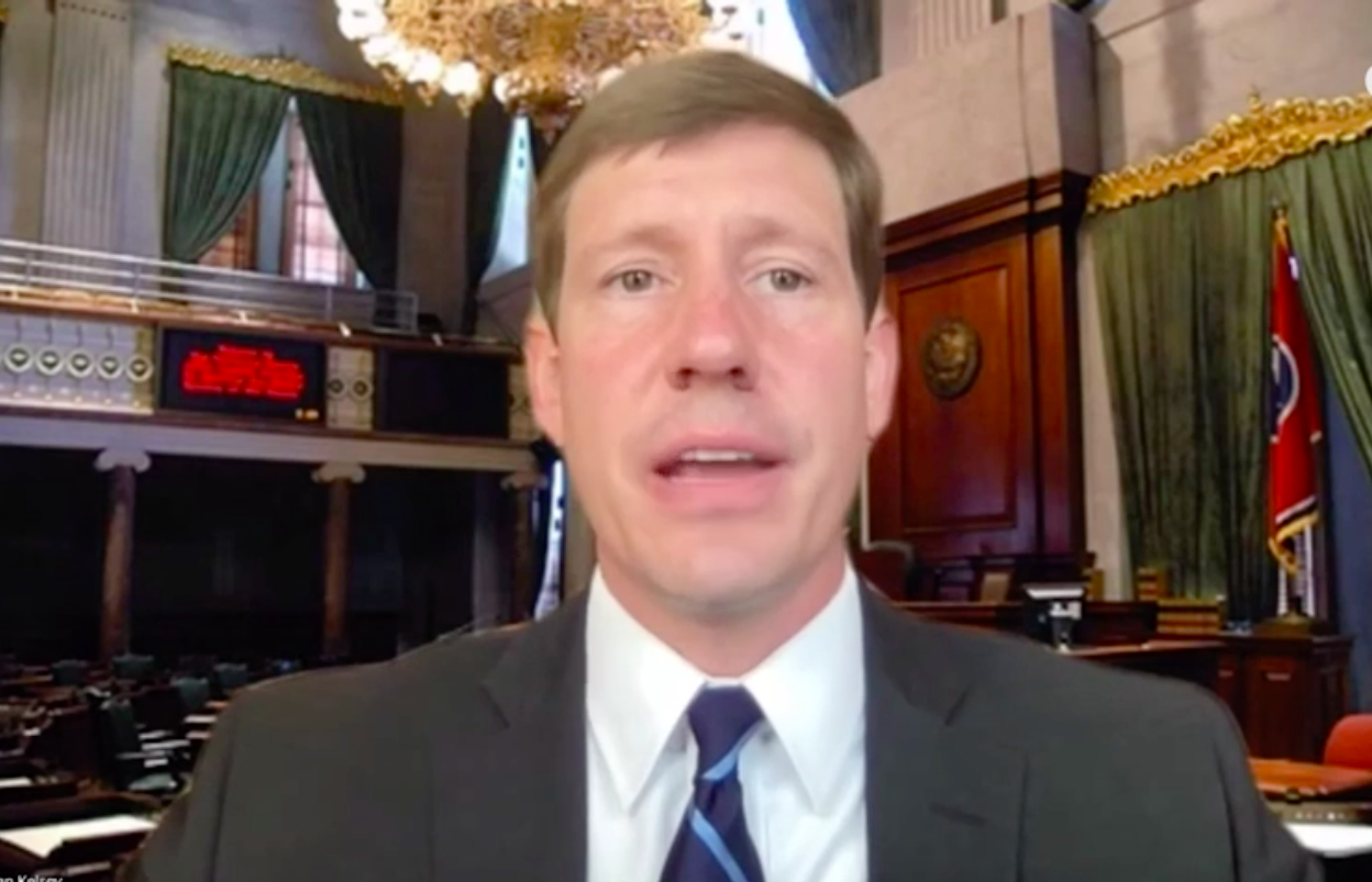 Man in suit and tie speaks in a legislative chamber.