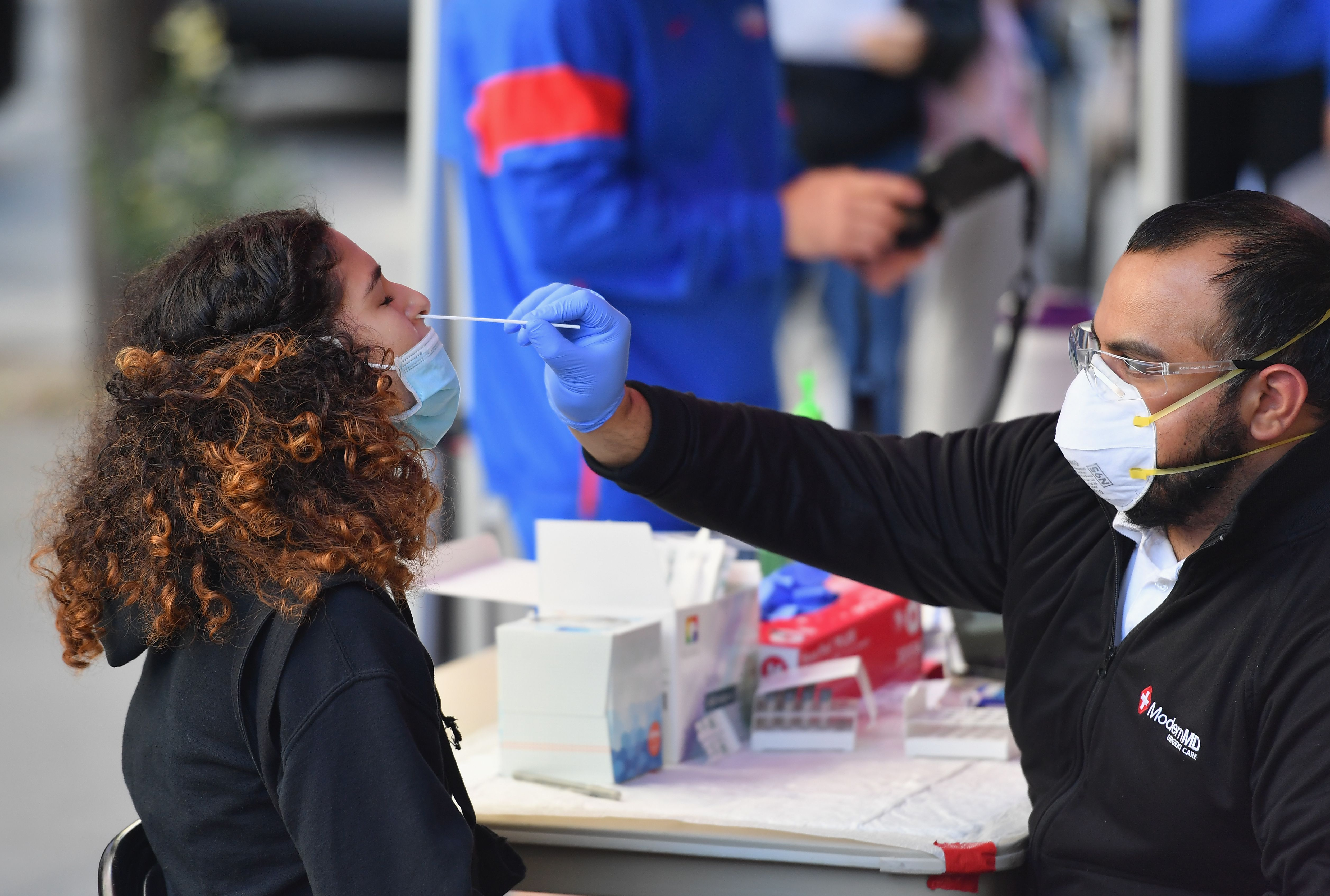 A student wearing a blue face mask is tested for COVID by a medical professional via nasal swab.