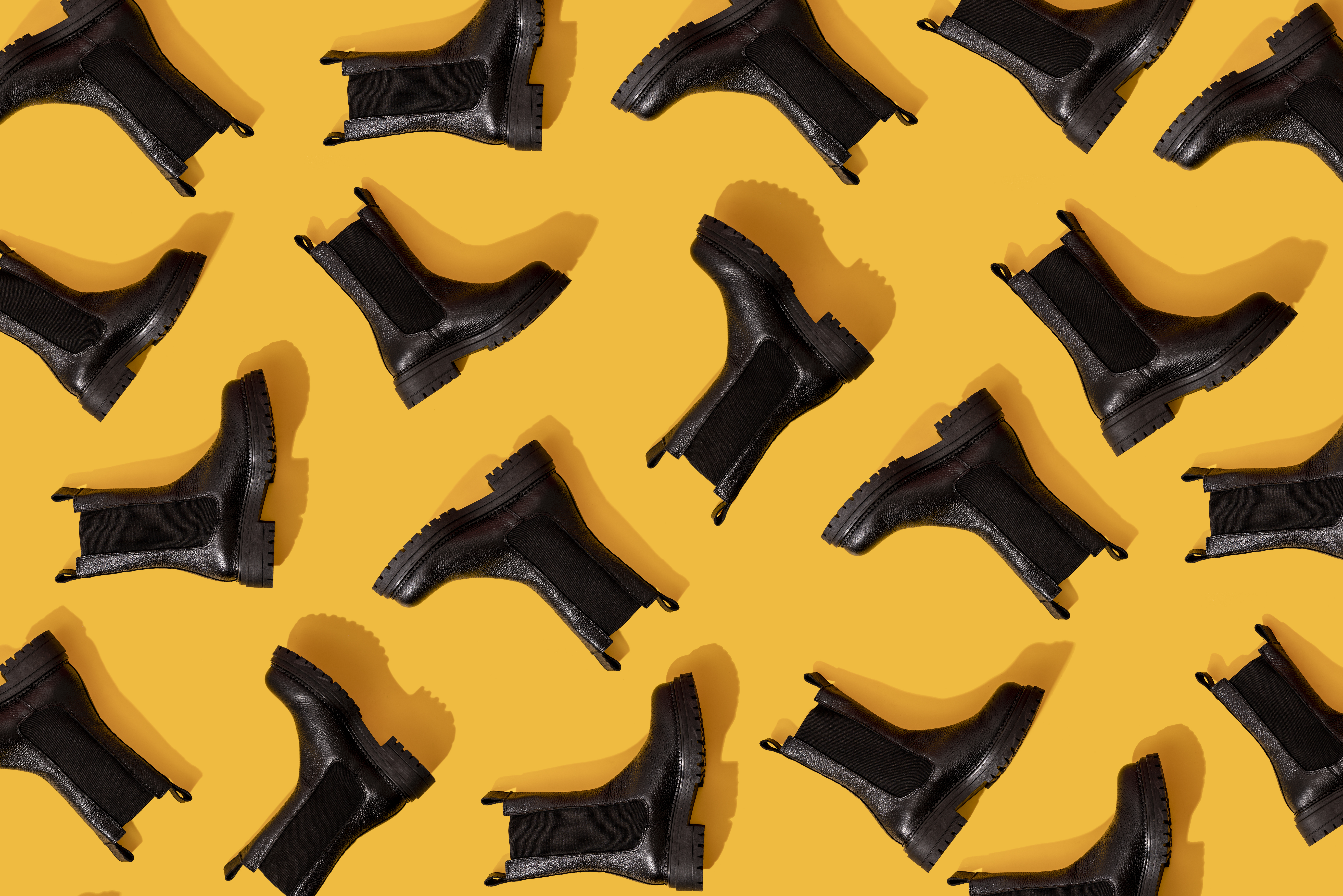 Black ankle boots arranged on a yellow background.