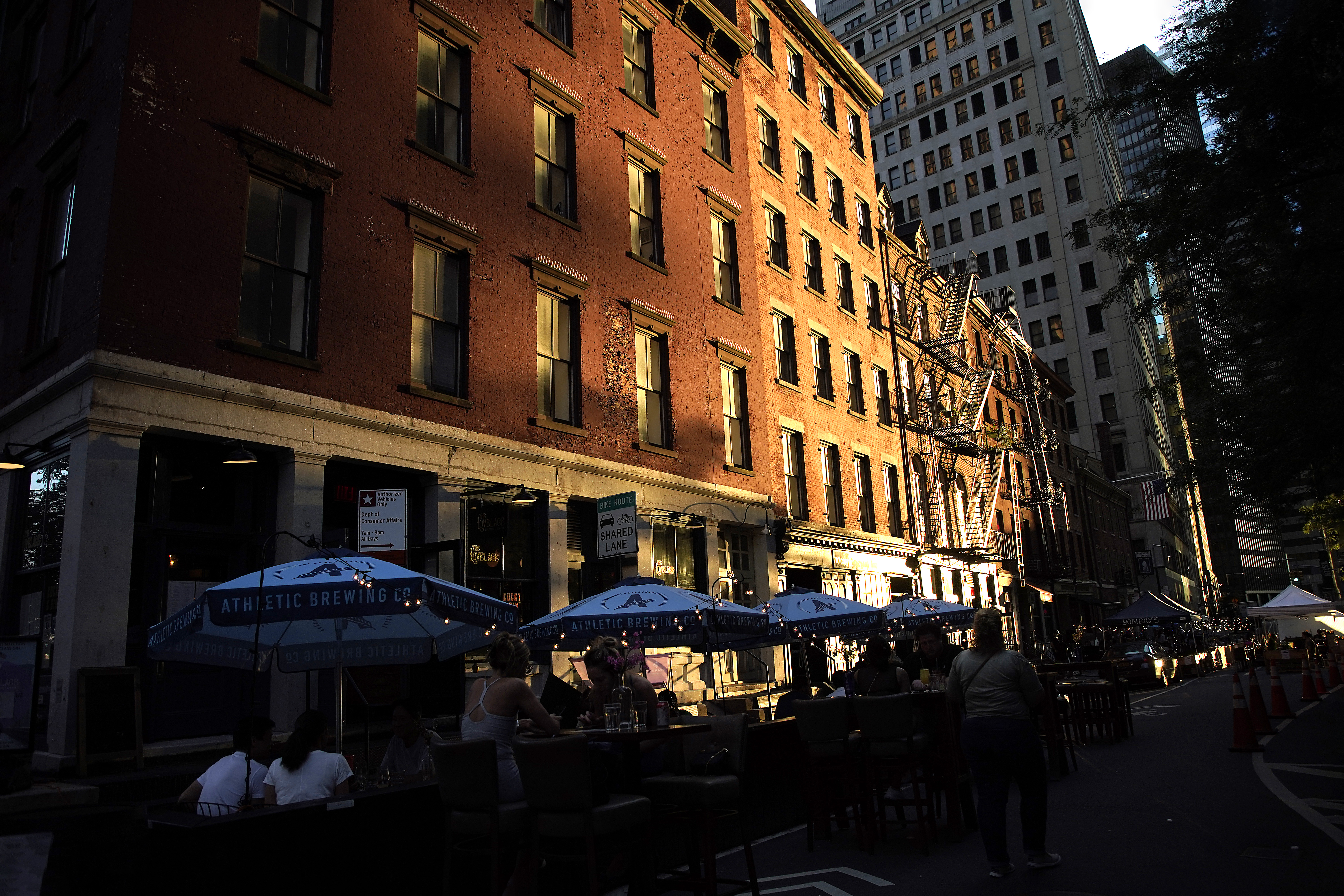 People dine at an outdoor restaurant located on the street in lower Manhattan.