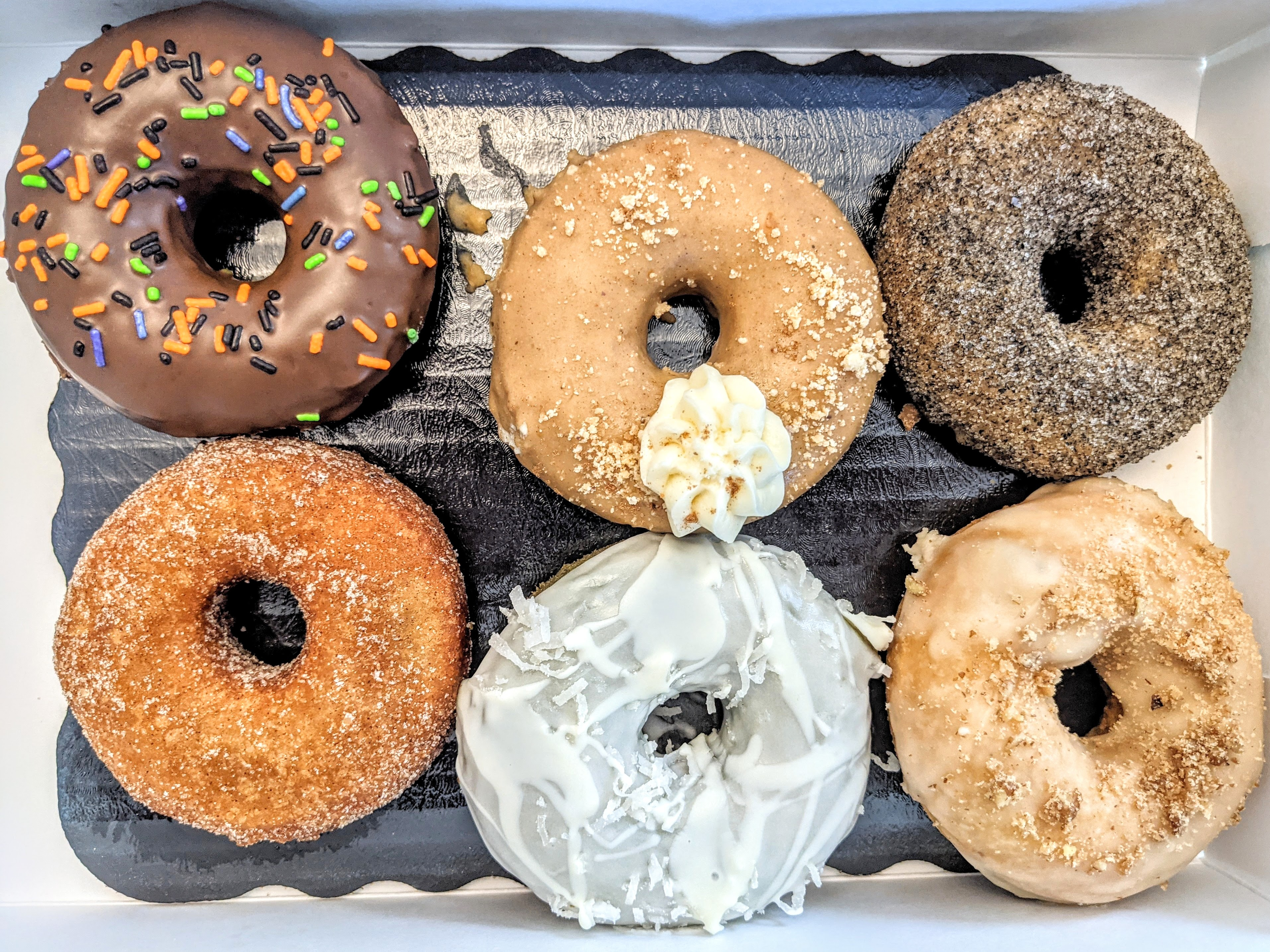 Overhead view of six doughnuts, all different flavors, in a white box.