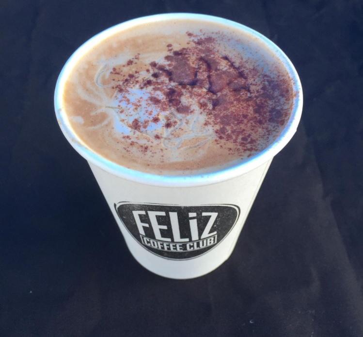 An espresso drink in a Feliz Coffee Club cup.