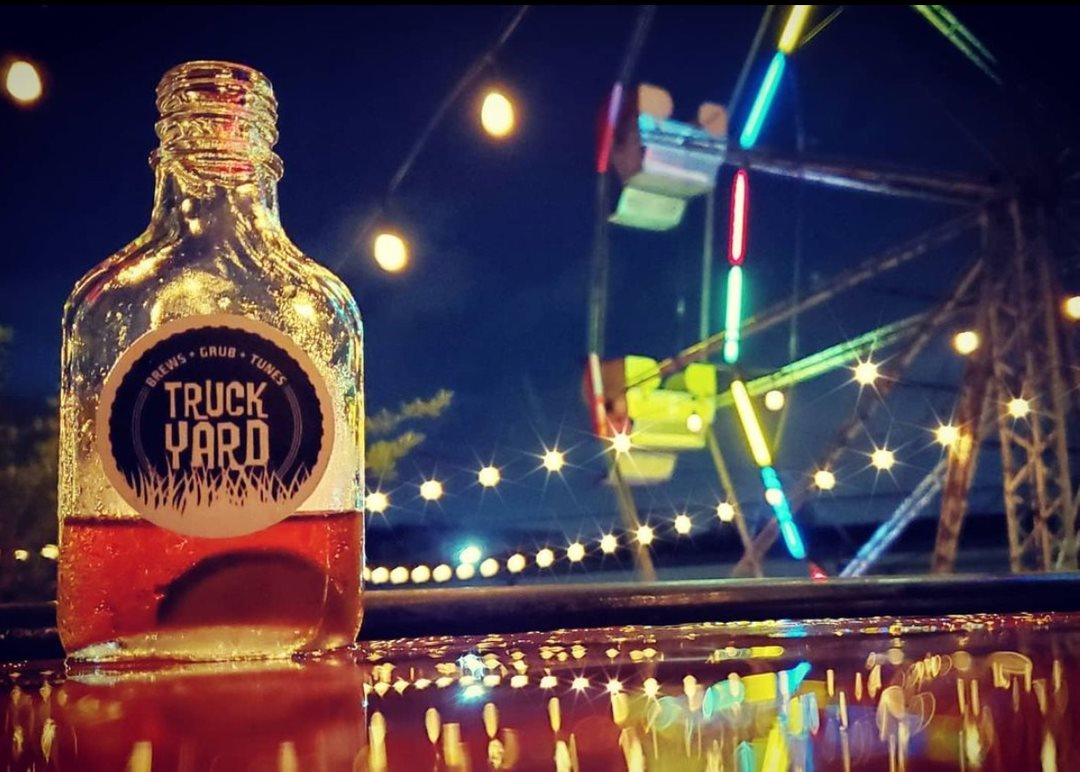 """A close up of a flask of booze that reads """"Truck Yard"""". In the background there is a Ferris wheel with lights that glow against a nighttime sky."""