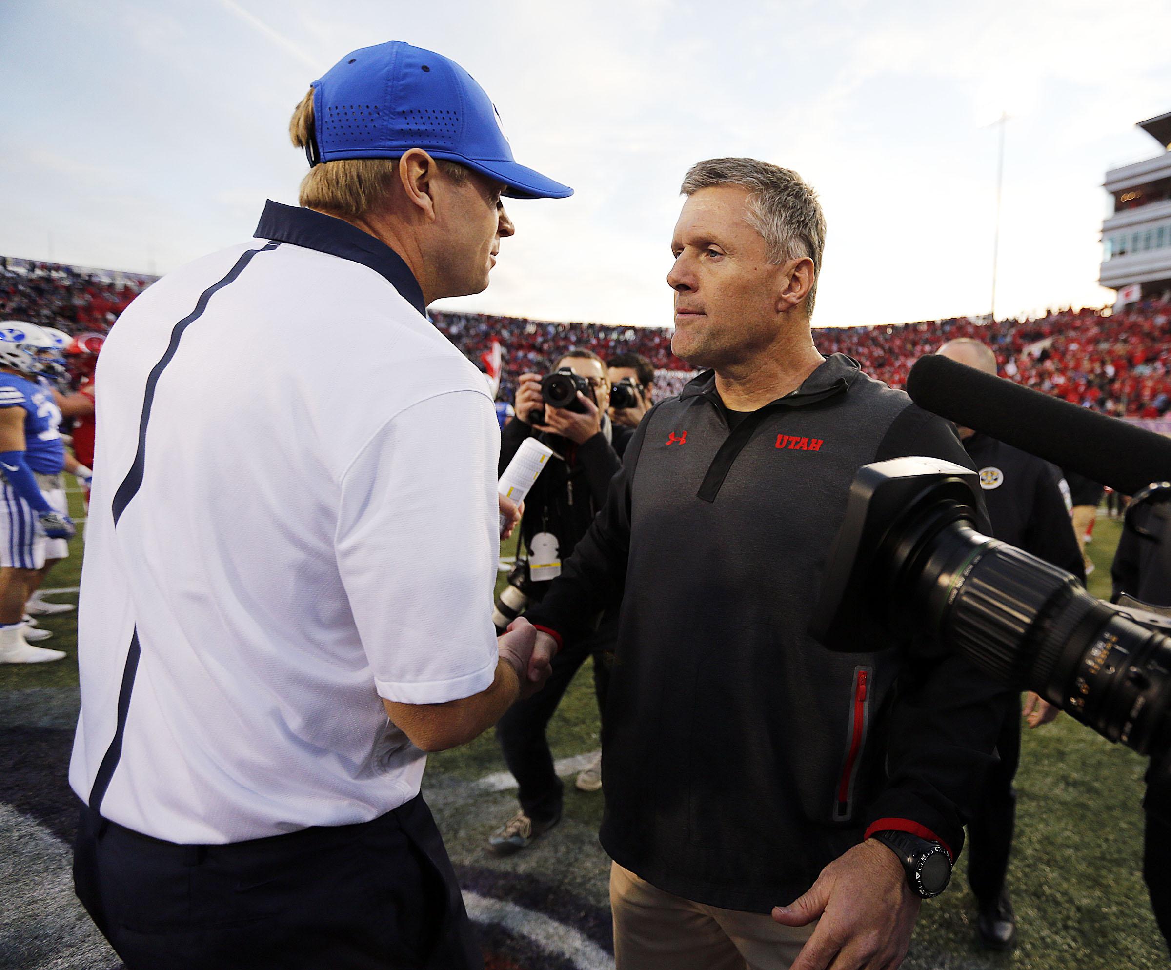 Brigham Young Cougars head coach Bronco Mendenhall, left, and Utah Utes head coach Kyle Whittingham meet following the Royal Purple Las Vegas Bowl.