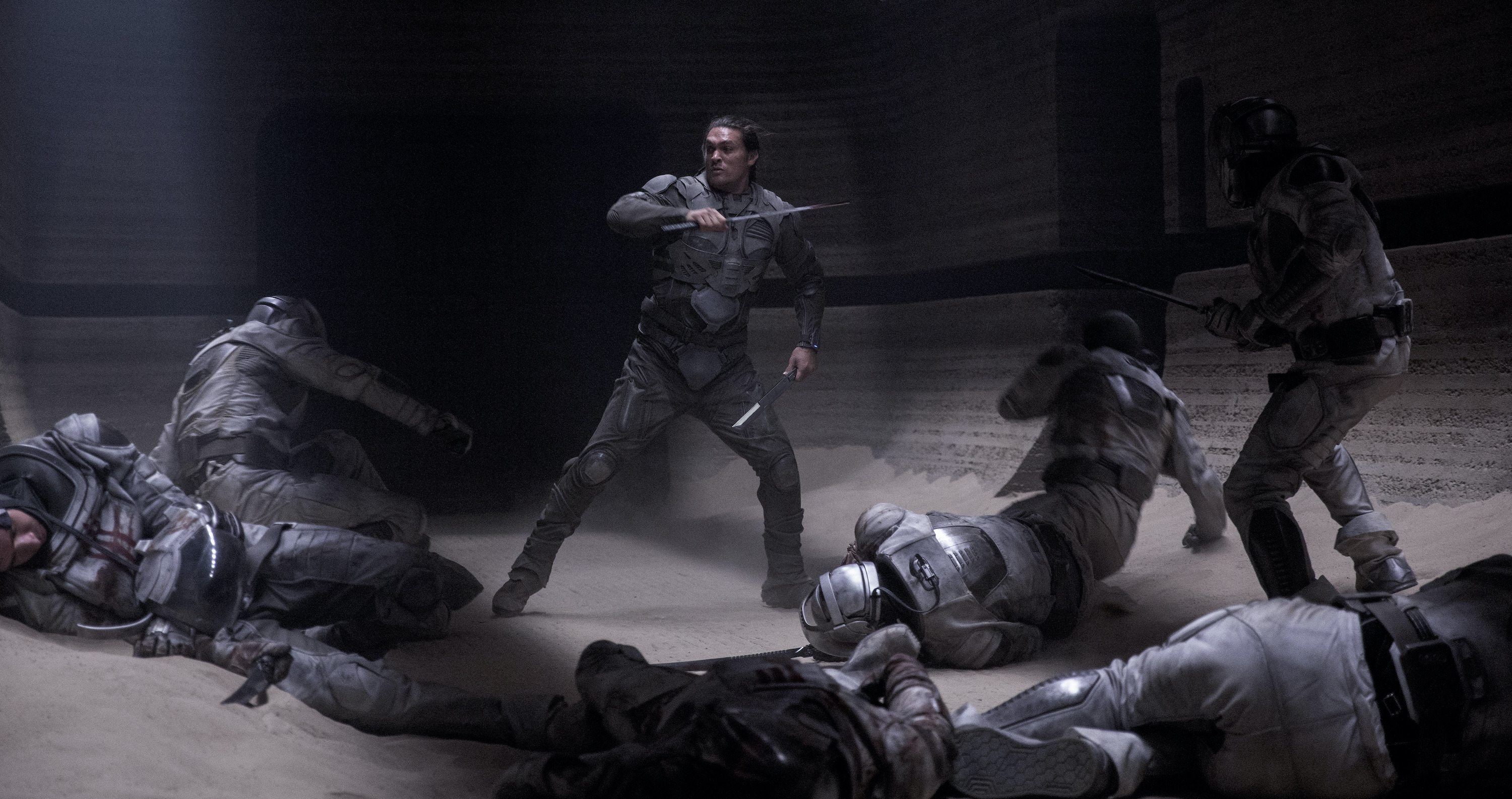 Jason Momoa as Duncan Idaho, wielding two blades and surrounded by collapsed or collapsing soldiers in grey armor in Dune