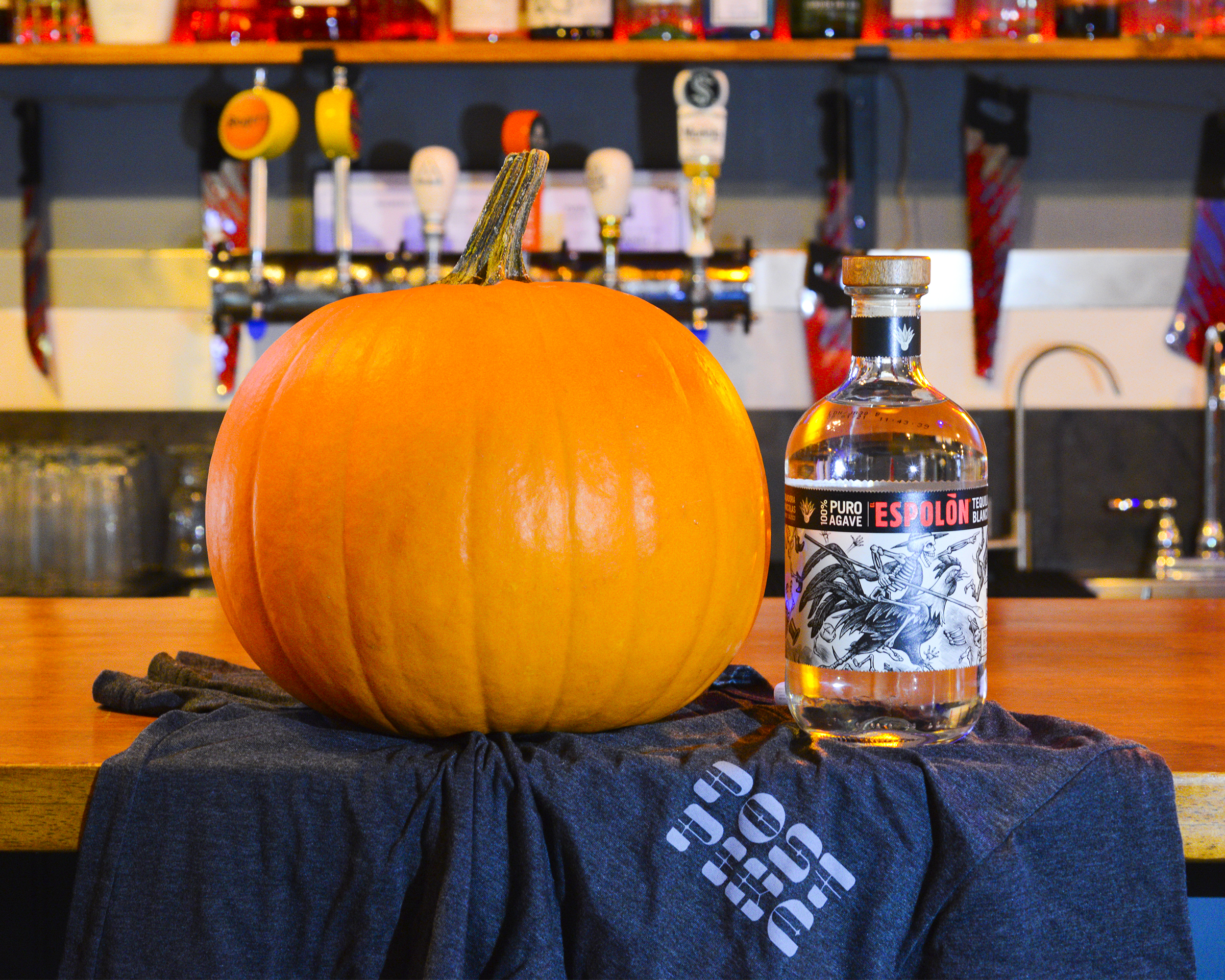 A large pumpkin sits next to a bottle of Espolon tequila. Both are on a black tablecloth with a bar in the background.