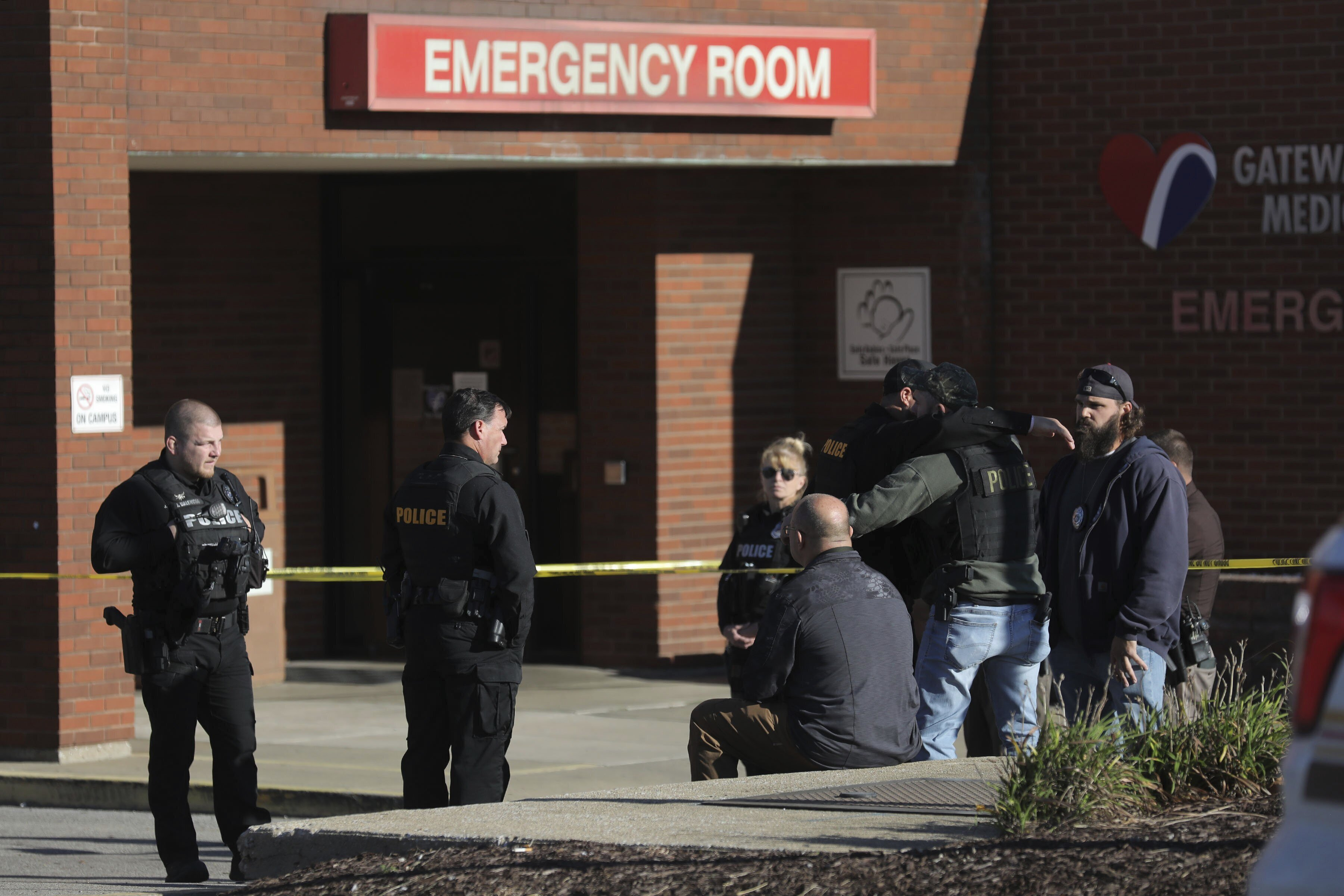 Police officers embrace while waiting outside the emergency room at Gateway Medical Center in Granite City, Ill., on Tuesday, Oct. 26, 2021.