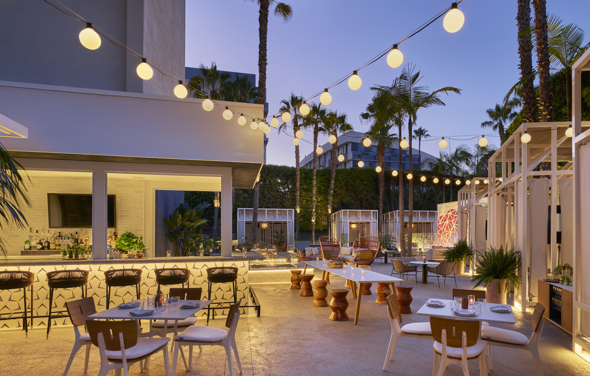 String lights and evening sunset at an outdoor restaurant bar with cabanas.