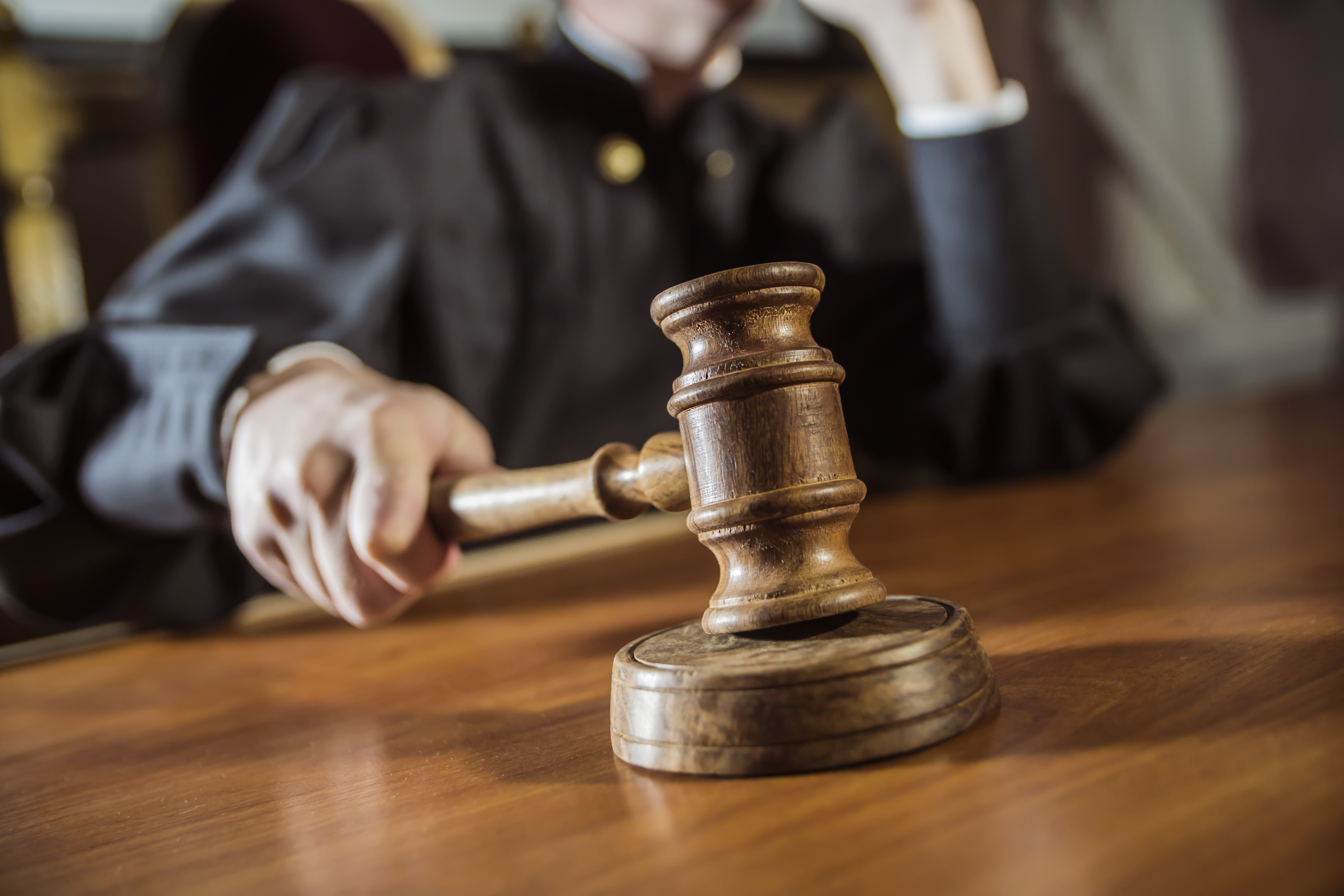 A judge bangs a gavel in this stock photo.