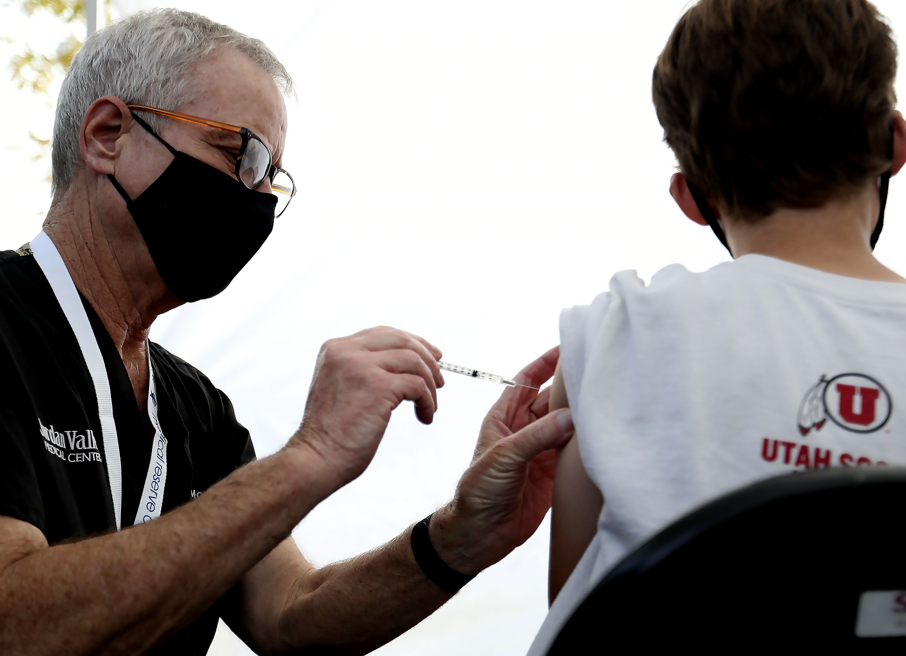 David McKay administers a COVID-19 vaccination to a 12-year-old boy at Rose Park Elementary in Salt Lake City on Wednesday, Sept. 22, 2021.