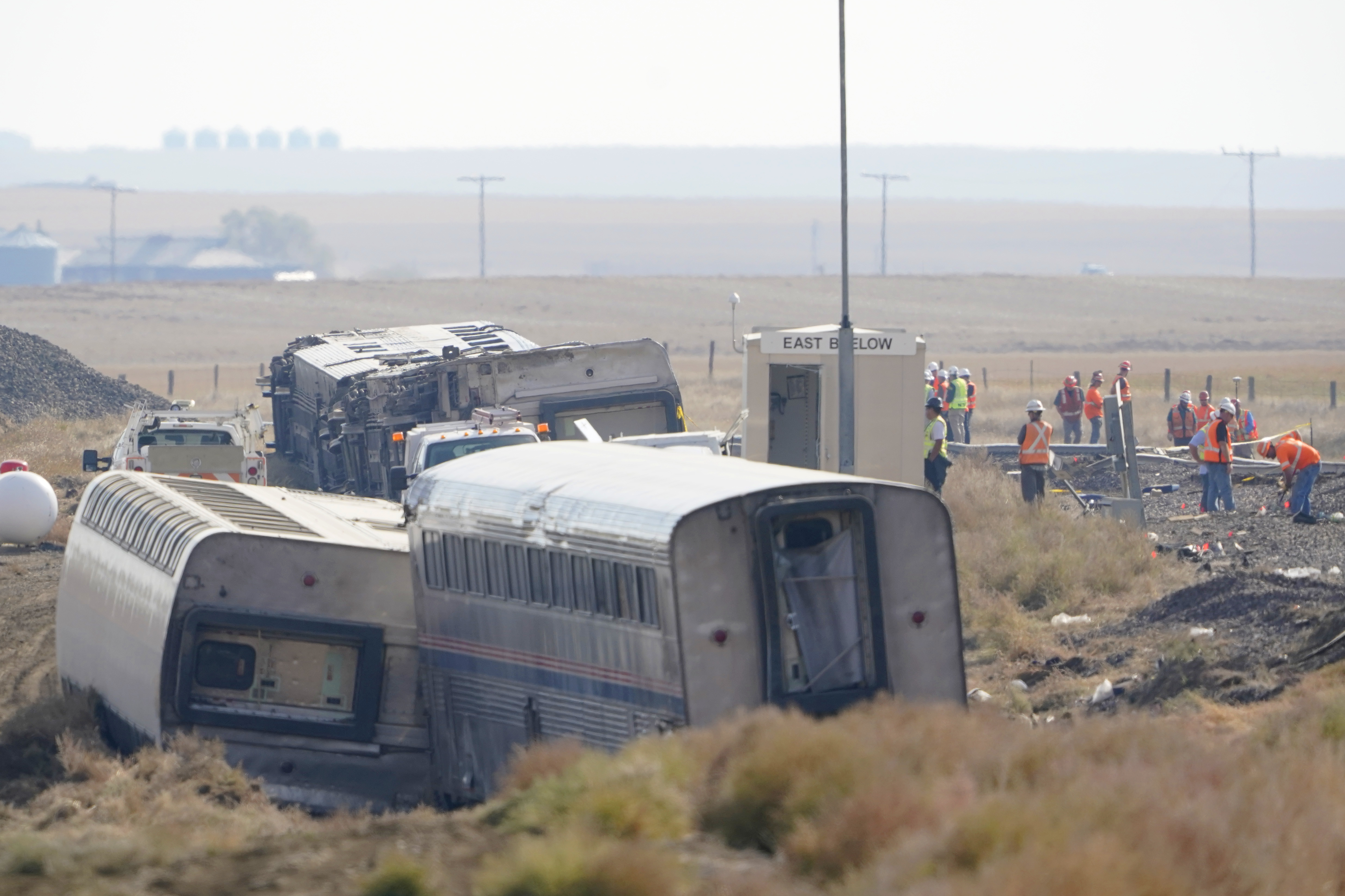 workers stand near train tracks next to overturned cars from an Amtrak train that derailed near Joplin, Mont.