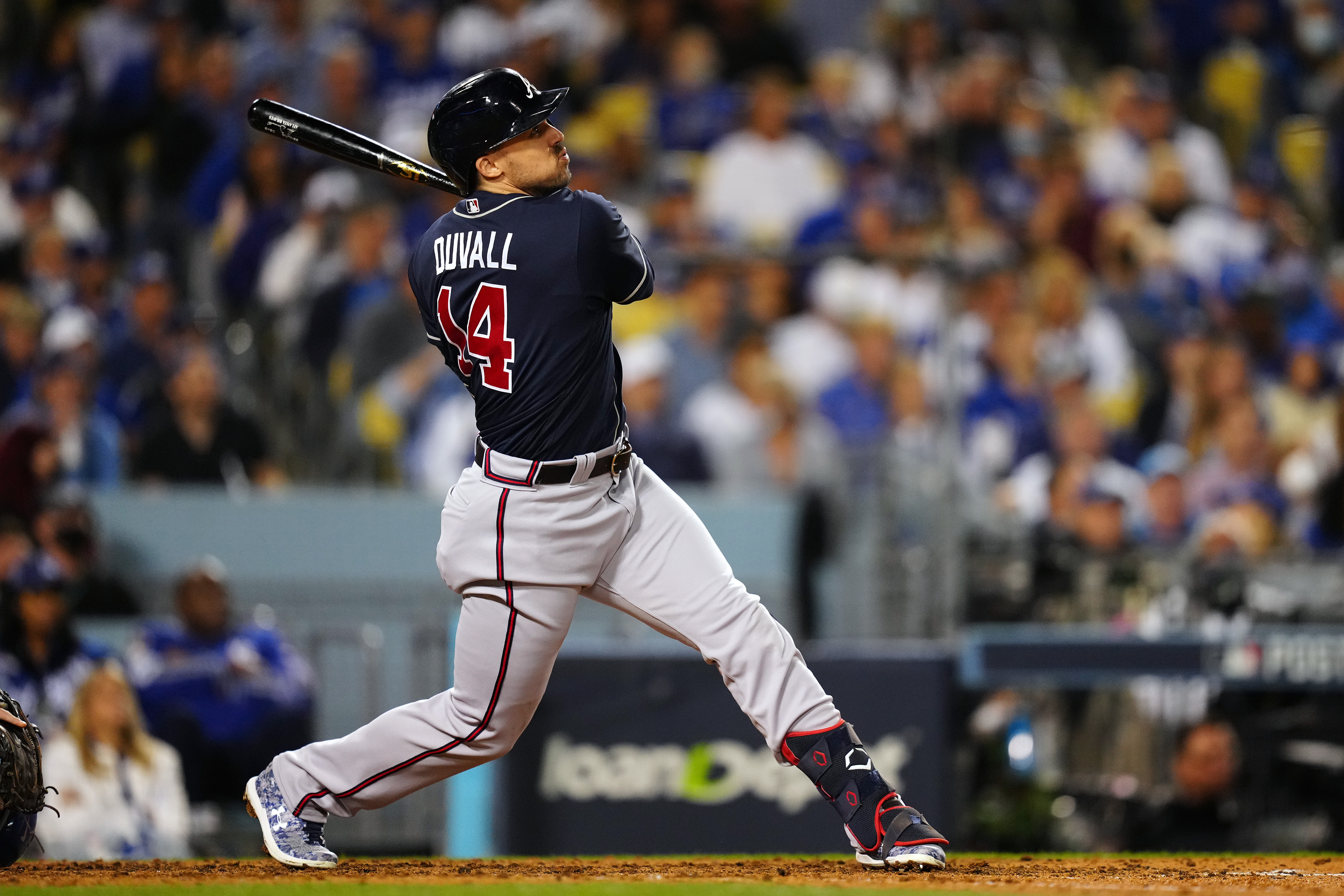 Adam Duvall #14 of the Atlanta Braves hits a sac fly to score Ozzie Albies #1 in the fifth inning during Game 4 of the NLCS between the Atlanta Braves and the Los Angeles Dodgers at Dodgers Stadium on Wednesday, October 20, 2021 in Los Angeles, California.