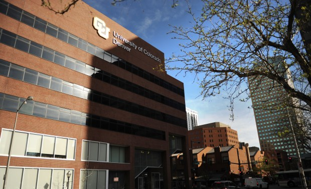 A building at the University of Colorado Denver campus against the backdrop of other city buildings and a blue sky.