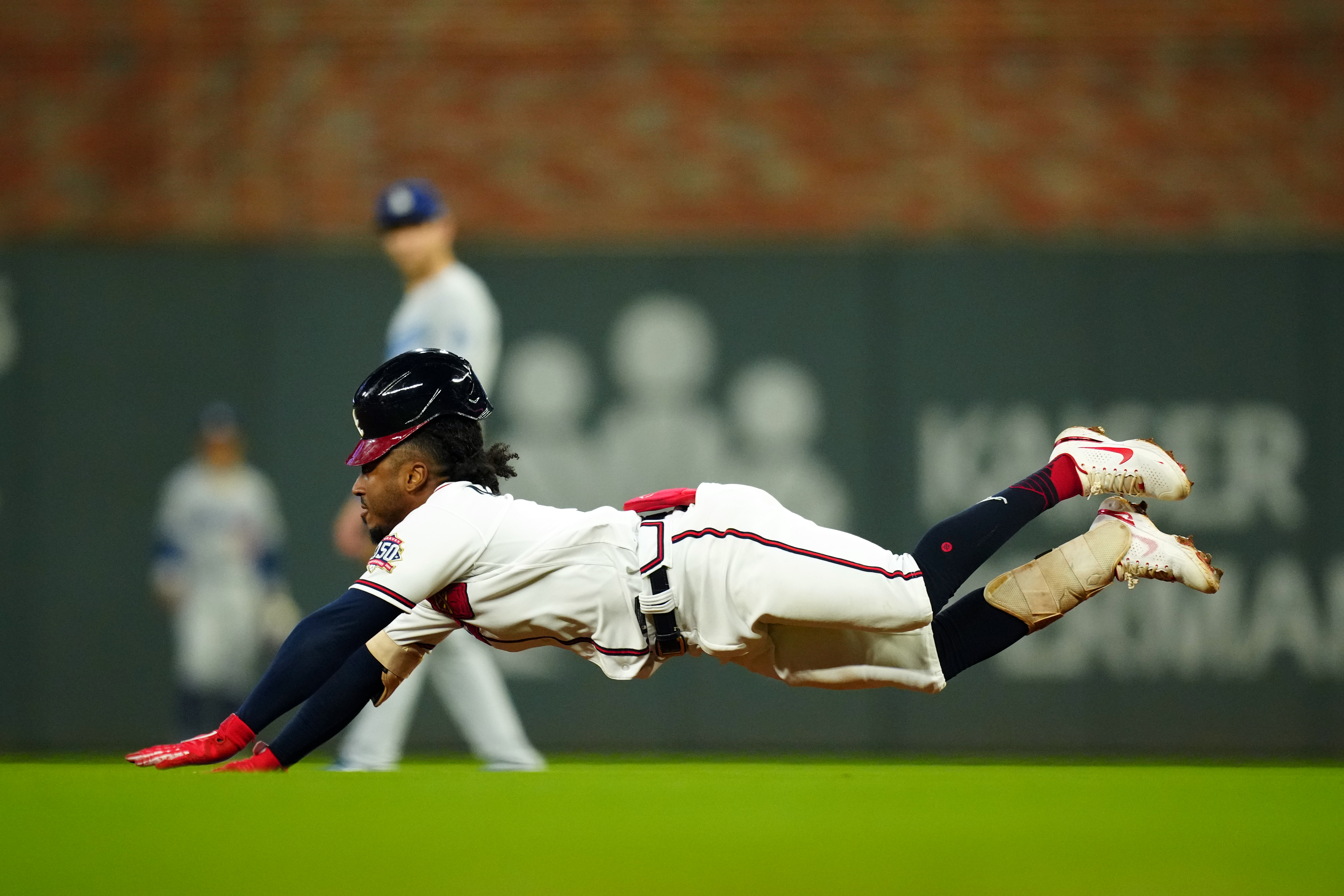 Ozzie Albies #1 of the Atlanta Braves slides safely into second base after hitting a double in the first inning of Game 6 of the NLCS between the Los Angeles Dodgers and the Atlanta Braves at Truist Park on Saturday, October 23, 2021 in Atlanta, Georgia.