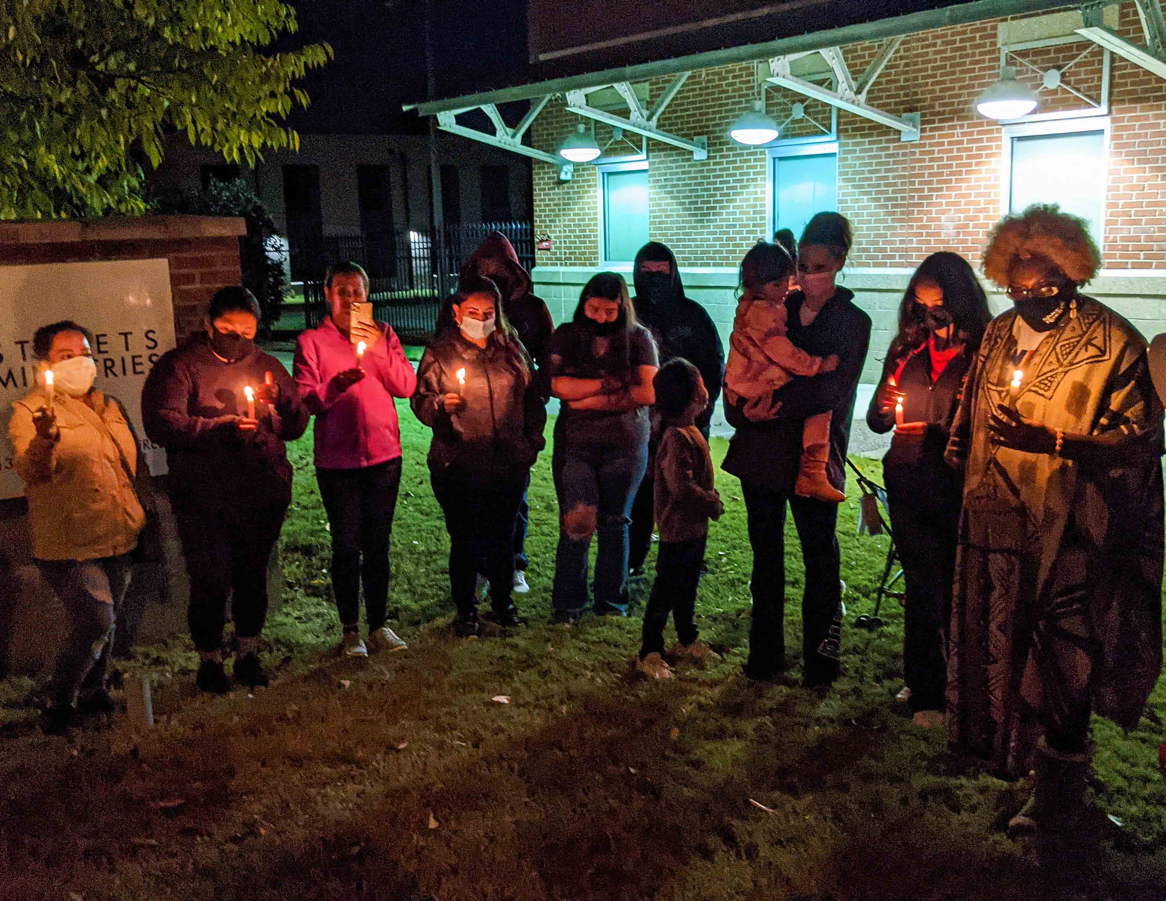 About a dozen people stand outside at night in a semi-circle holding candles during a candlelight vigil in front of a community center.