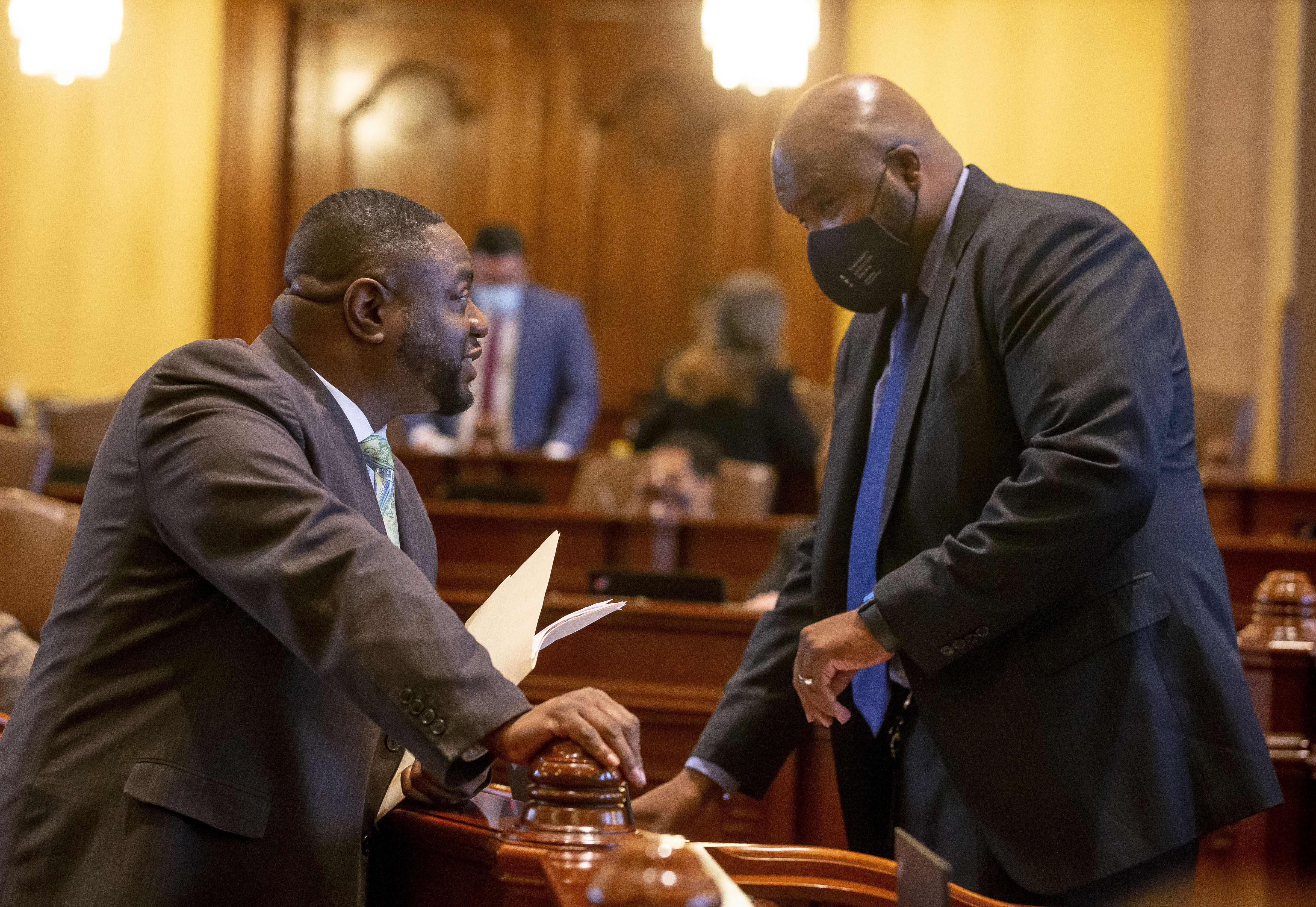 State Sen. Emil Jones III, D-Chicago, left, speaks with state Sen. Elgie Sims Jr., D-Chicago, right, on the floor of the Senate in May.