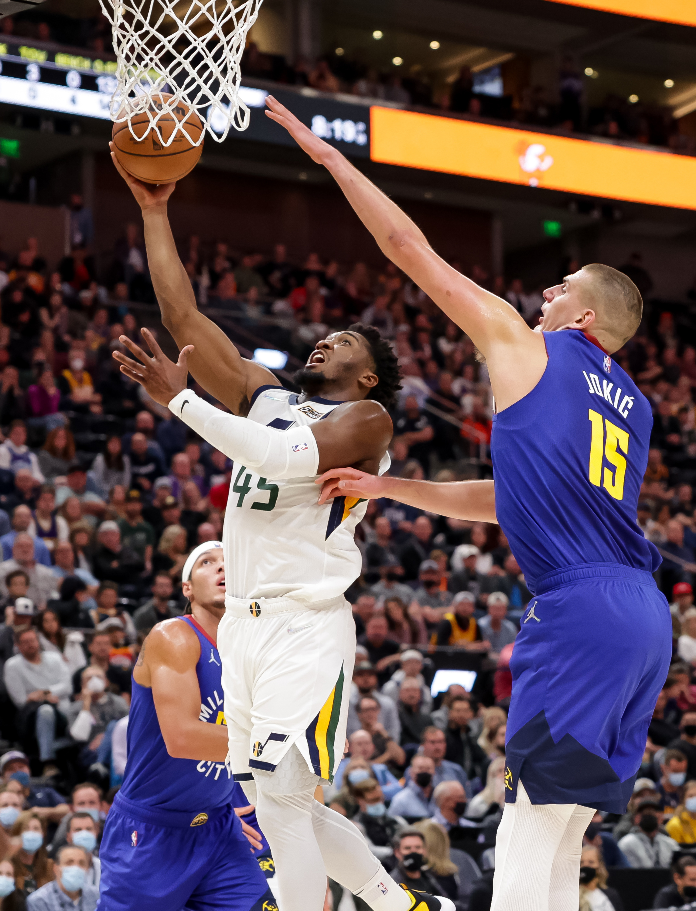 Utah Jazz guard Donovan Mitchell, wearing a white jersey, goes to the hoop ahead of Denver Nuggets center Nikola Jokic, wearing a blue jersey, during the game
